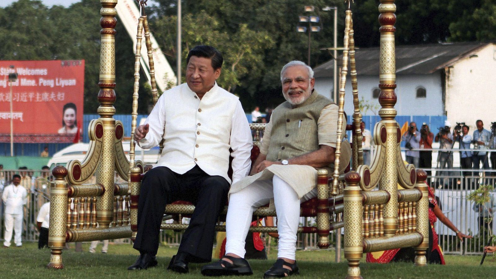 Chinese President Xi Jinping, left and Indian Prime Minister Narendra Modi, sit on a traditional swing at the Sabarmati River front in Ahmadabad, India, Wednesday, Sept. 17, 2014. Xi landed in the Indian prime minister's home state of Gujarat on Wednesday for a three-day visit expected to focus on India's need to improve worn out infrastructure and reduce its trade deficit. (AP Photo/Press Trust of India) INDIA OUT