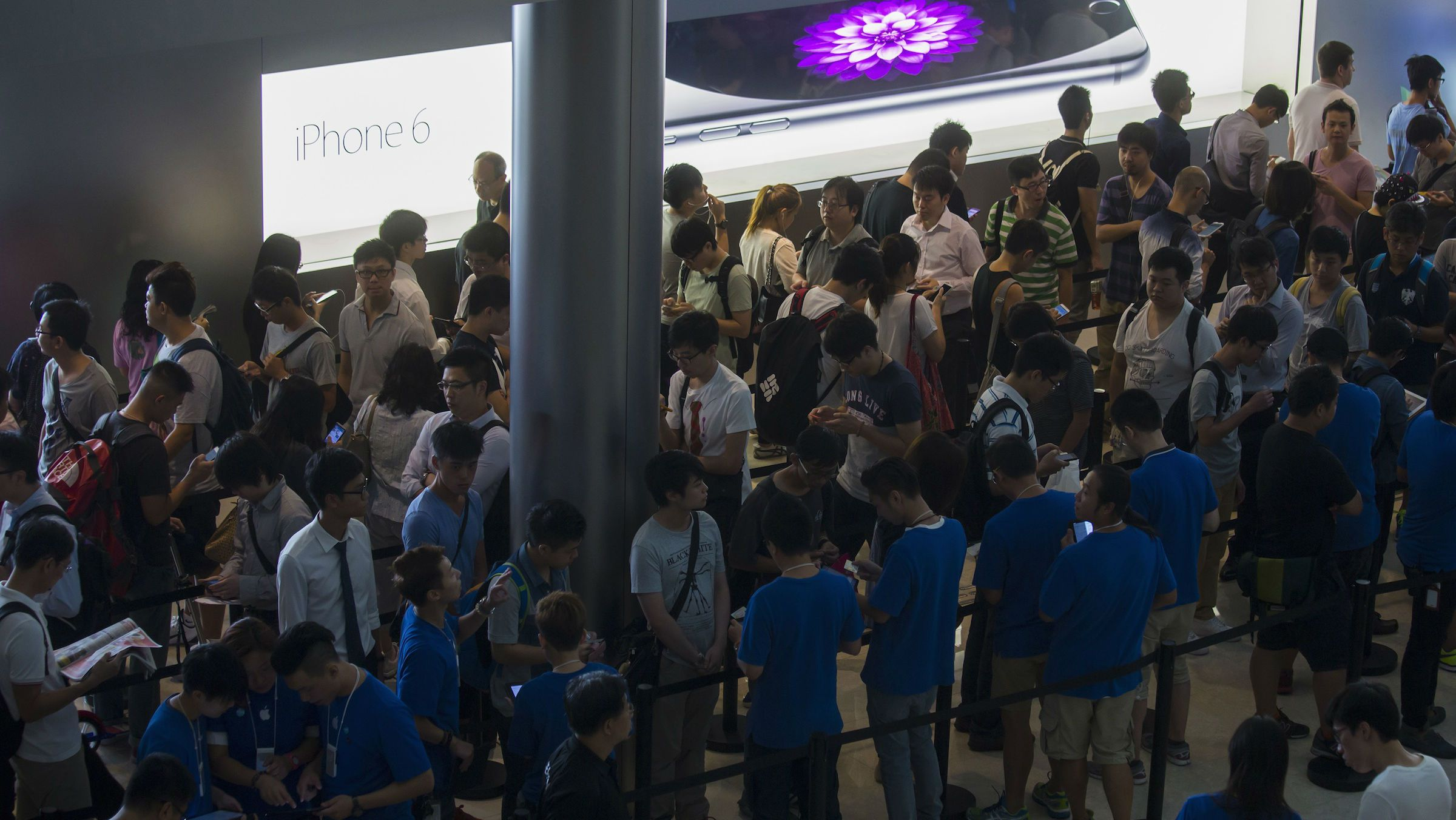 Customers stand in a line on the first day of sale for the iPhone 6 and iPhone 6 Plus, outside the Apple store in Hong Kong
