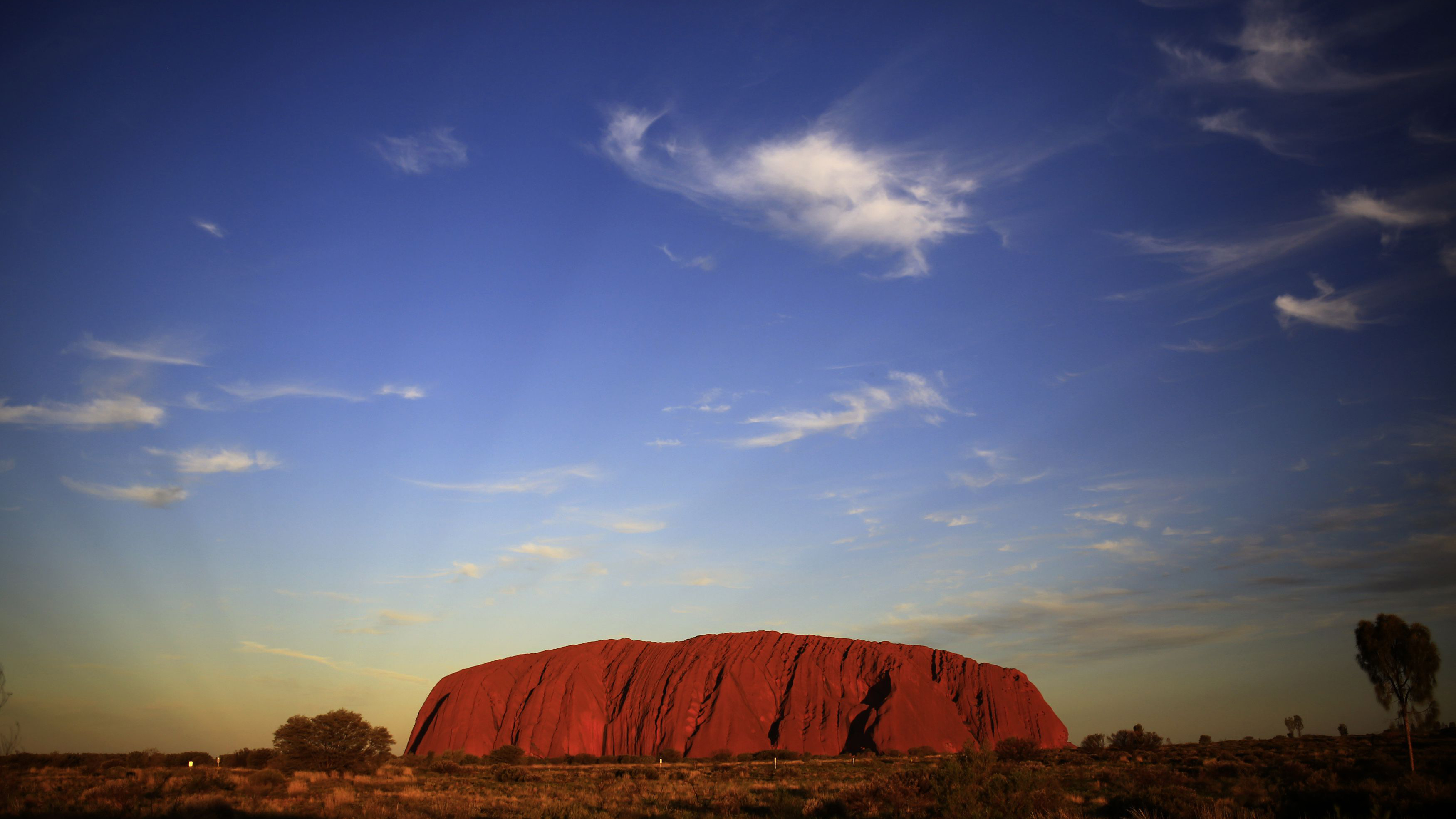 Uluru is lit by the setting sun in the Northern Territory in central Australia April 21, 2014. REUTERS/Phil Noble (AUSTRALIA - Tags: ENVIRONMENT TRAVEL)