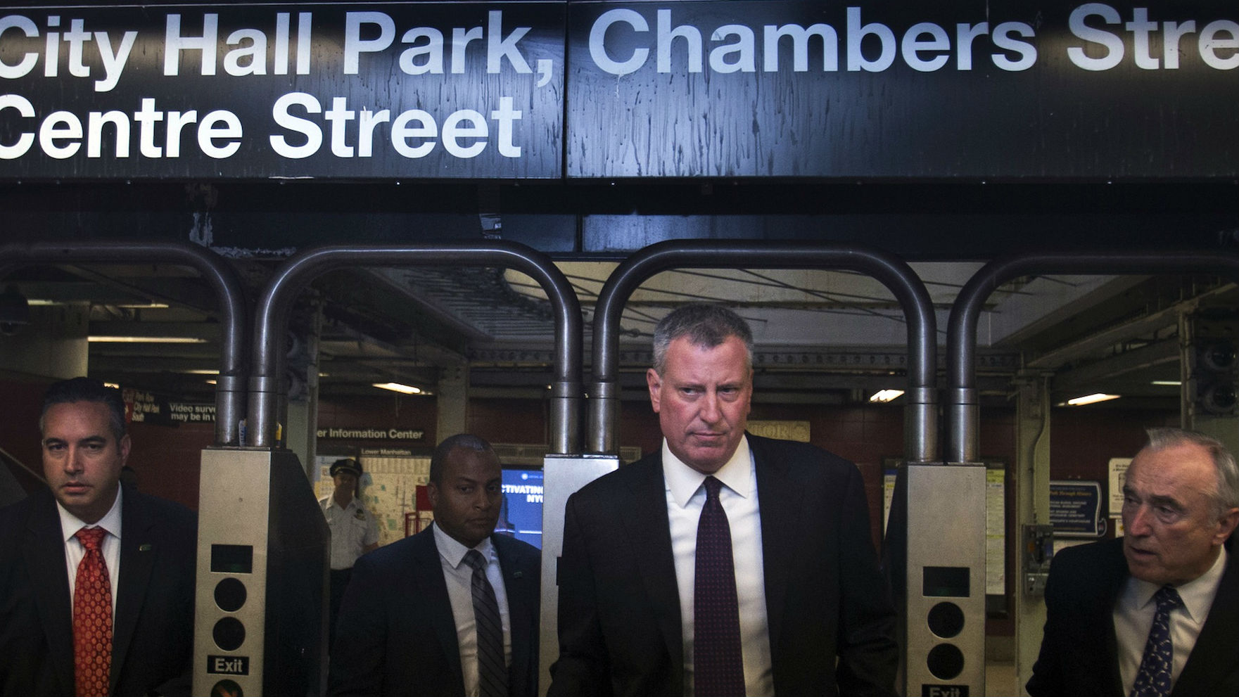 New York Mayor Bill de Blasio (2nd R) and New York City Police Commissioner William Bratton (R) enter the City Hall subway station while on their way to give a news conference in New York September 25, 2014