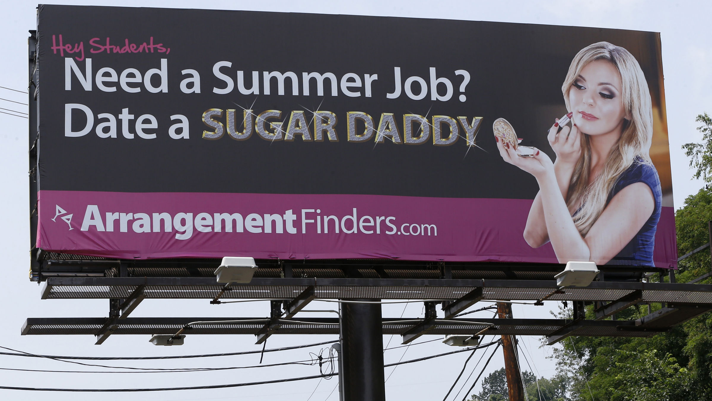 "A billboard that a Toronto company says is meant to connect female college students with ""sugar daddies"" who pay a fee to join its website service is seen on Wednesday, July 10, 2013, in Pittsburgh. Pennsylvania State police Cpl. Raymond Schafer, who works for a western Pennsylvania vice squad, confirmed the ads are legal because, as Perkins contends, they don't include a direct offer of money for sex."