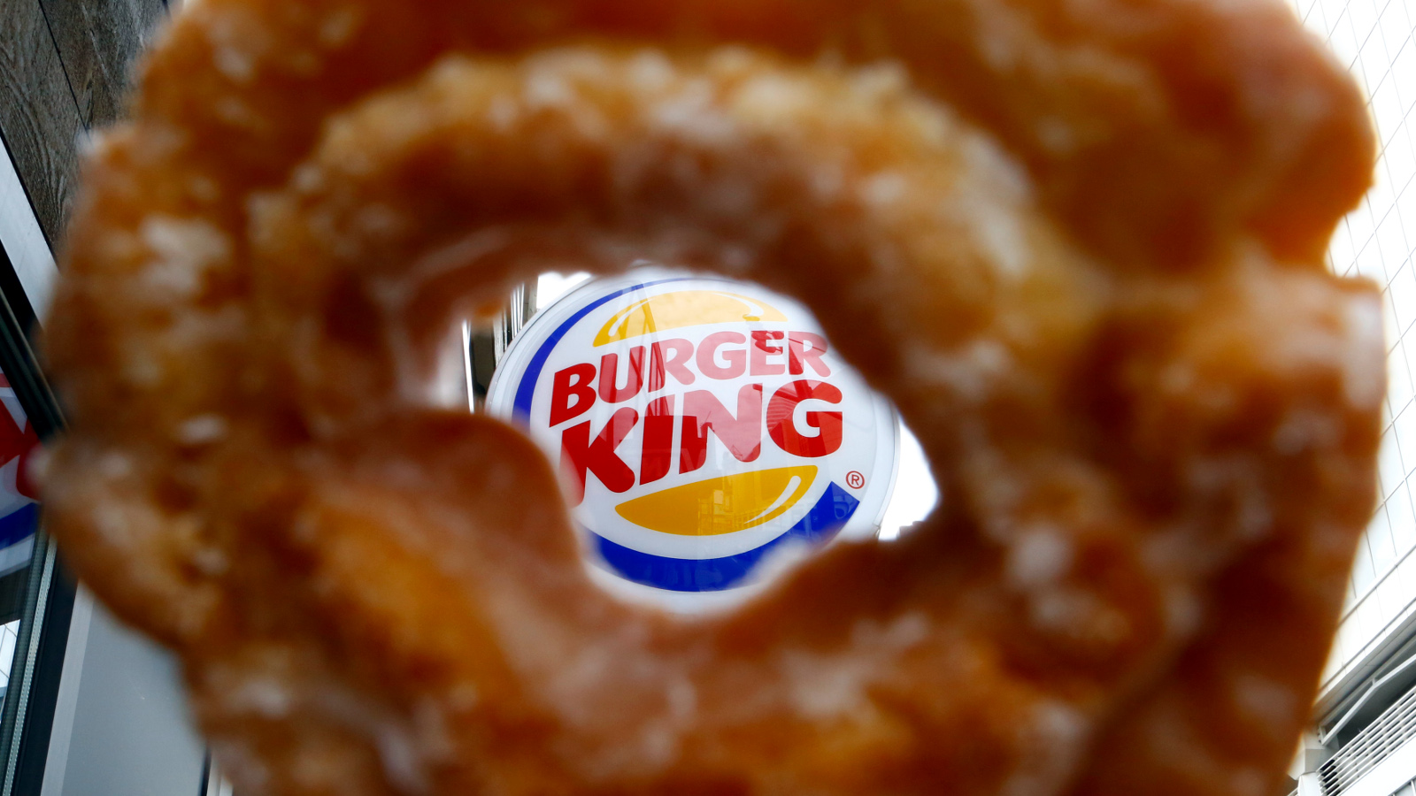 The Burger King logo is seen through a Tim Horton's doughnut hole in a photo illustration outside a restaurant in Toronto August 29, 2014. Burger King's proposed $11.5 billion acquisition of Canada's Tim Hortons may offer big tax benefits to the U.S. fast food chain but the real tax winner is likely to be its controlling shareholder, 3G Capital. The New York investment firm is not only deferring a capital gains tax hit in the U.S. because of the deal structure, but is also poised to reap a multitude of dividend tax and other benefits by moving Burger King's domicile to Canada, tax experts on both sides of the border said.