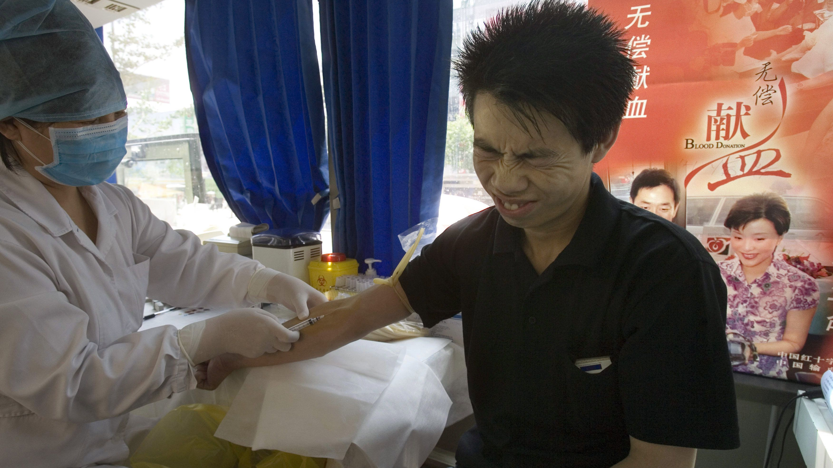 A Chinese man gets his blood tested prior to donating at a mobile blood center in Beijing, China, Wednesday, June 14, 2006. China marks World Blood Donor Day to encourage the habit of voluntary blood donations. China has launched repeated campaigns to clean up its blood-supply industry since unsanitary blood selling practices infected thousands of people in the central province of Henan with AIDS in the 1990s. (AP Photo/Ng Han Guan)
