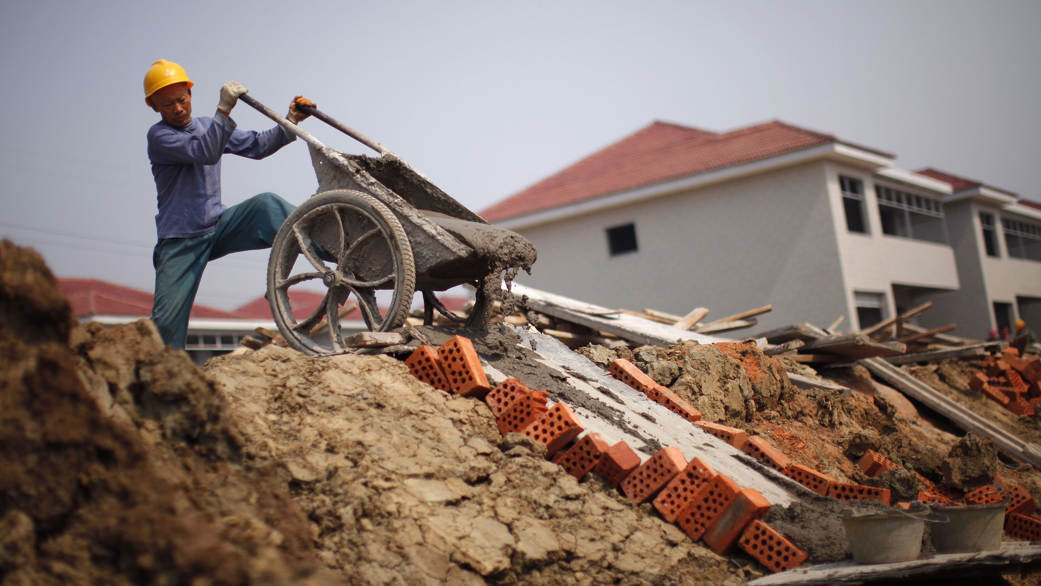 """A labourer pours cement at a construction site for new houses in Huaxi village, Jiangsu province October 8, 2011. As housing bubbles go, China's looks relatively benign. Unlike in the United States, Chinese home buyers typically put down at least 40 percent of the purchase price. That means they don't have to worry about a modest decline wiping out all their equity, and banks have little reason to fear an influx of """"jingle mail"""" from defaulting homeowners returning the keys. To match Insight ECONOMY-CHINA/PROPERTY REUTERS/Carlos Barria (CHINA - Tags: BUSINESS REAL ESTATE EMPLOYMENT CONSTRUCTION)"""