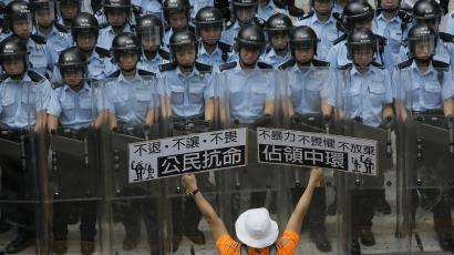 "A protester raises placards that read ""Occupy Central"" and ""Civil disobedience"" in front of riot policemen outside the government headquarter in Hong Kong, Saturday, Sept. 27, 2014. Riot police in Hong Kong on Saturday arrested scores of students who stormed the government headquarters compound during a night of scuffles to protest China's refusal to allow genuine democratic reforms in the semiautonomous region. (AP Photo/Vincent Yu"