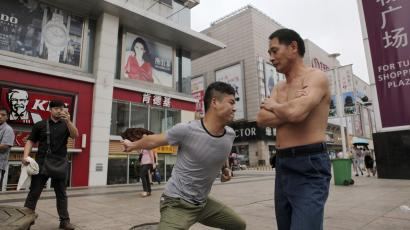 china gdp slowdown factory industrial production output economy economic li keqiang zhou xiaochuan debt crisis stimulus banking lending credit electricity Xie Shuiping (R) is punched by a man as part of a challenge in Nanchang, Jiangxi province, August 18, 2014. Xie, 48, has been challenging people to punch his belly for more than ten years. He has promised to give the challenger 1,000 yuan ($163) if they can make him fall or step back from being punched but only one person has managed to do so thus far, according to local media. Picture taken August 18, 2014. REUTERS/Stringer