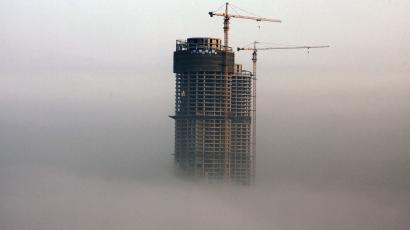 A building under construction is seen in fog in Rizhao, Shandong province, February 26, 2014. China's property market is likely to see at most a moderate correction in prices in some small cities this year, according to a Reuters straw poll of 13 industry watchers this week, with the chance of a sharp fall in prices nationwide very slim. Picture taken February 26, 2014. REUTERS/Stringer