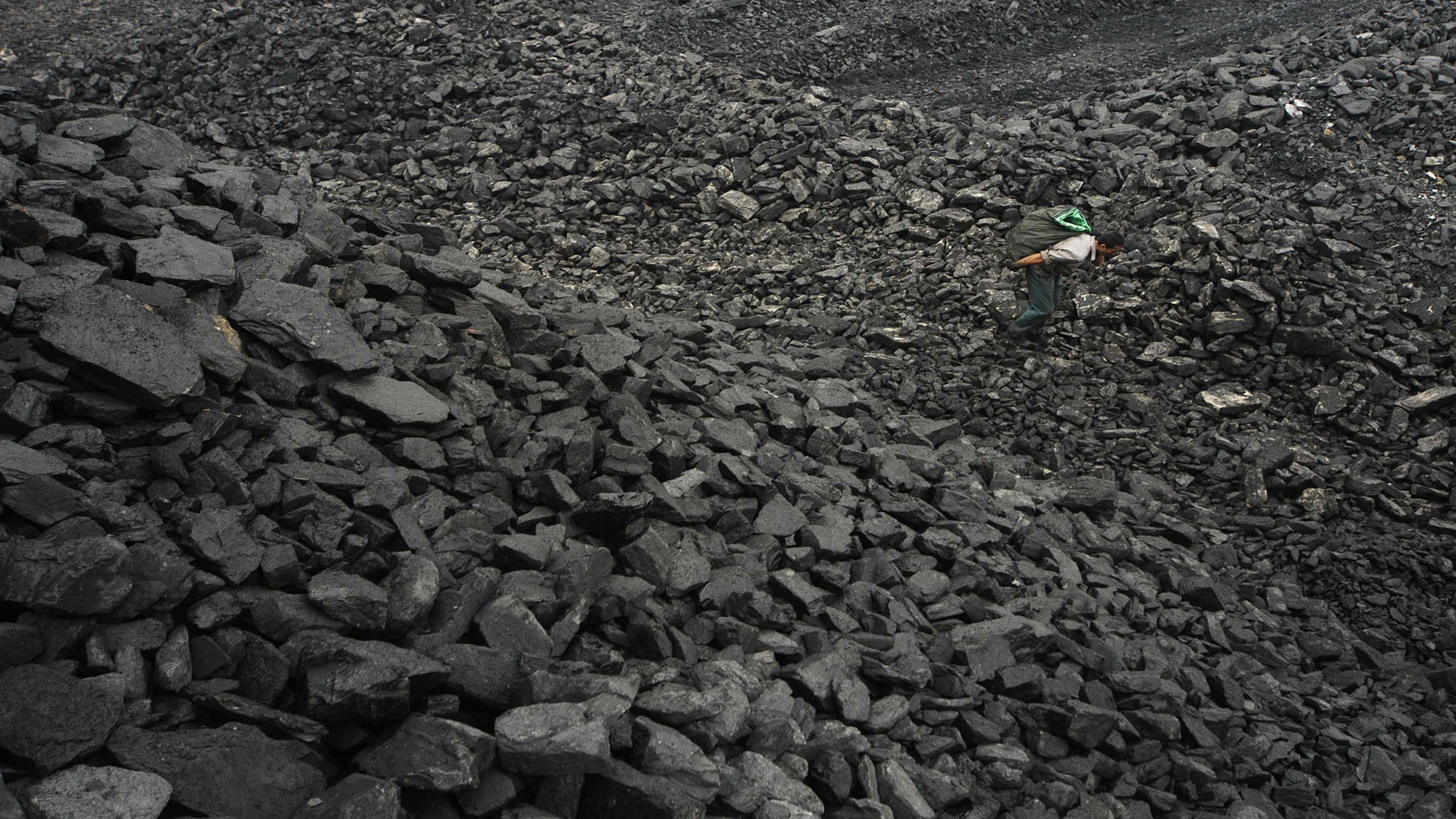 A labourer looks for usable coal at a cinder dump site on the outskirts of Changzhi, north China's Shanxi province August 10, 2007.