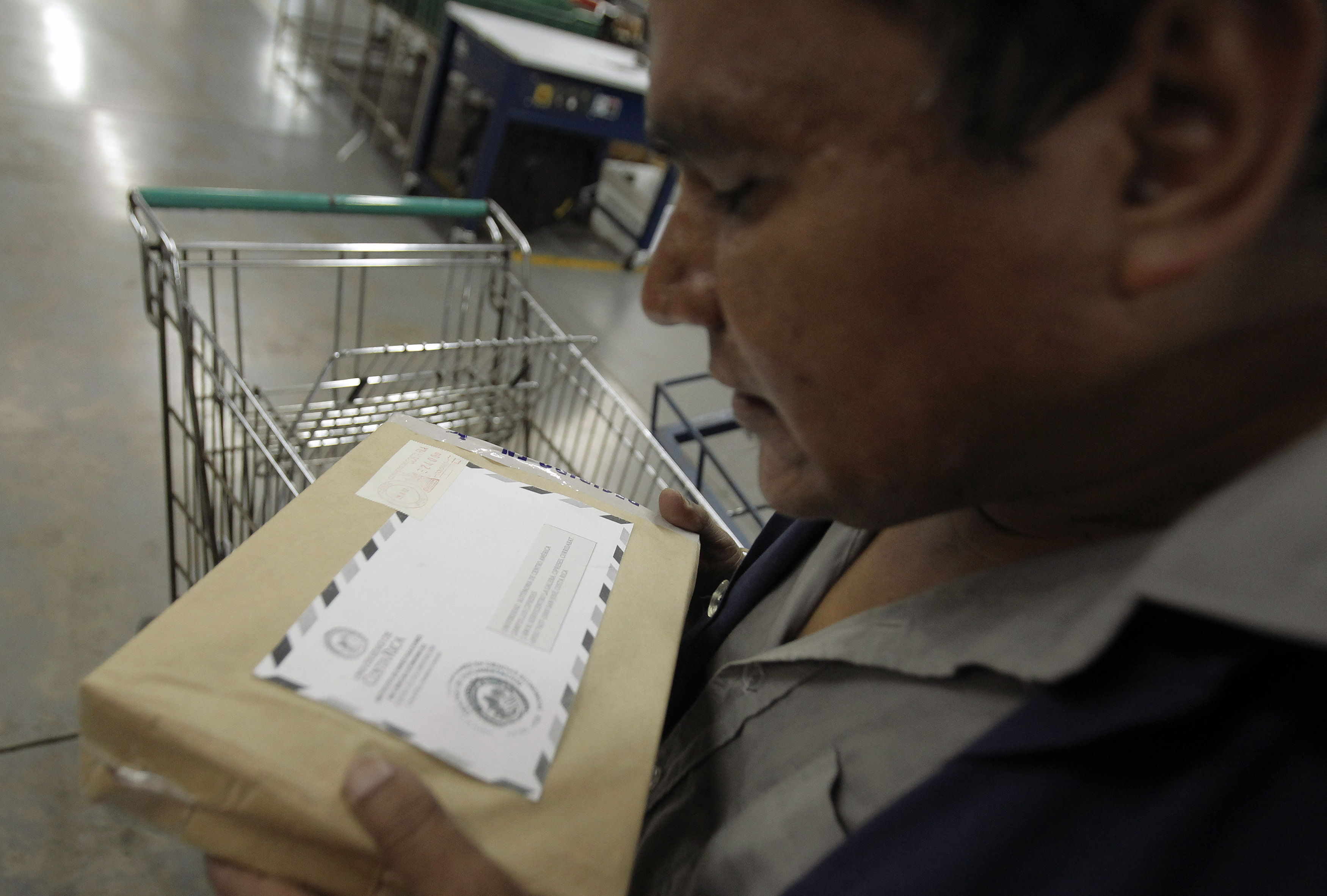 A worker tries to decipher an address on a letter at the post office in San Jose September 27, 2012. Costa Rica, unveiled plans on Thursday to install its first street signs, so residents will not have to cite local landmarks like fast-food chains or gas stations when giving directions. Municipal workers will install about 22,000 signs and plaques on street corners in the city, home to 1.4 million people, where the current informal system is tolerated by residents, but creates headaches for visitors and the post office. REUTERS/Juan Carlos Ulate (COSTA RICA - Tags: SOCIETY POLITICS) - RTR38ILQ