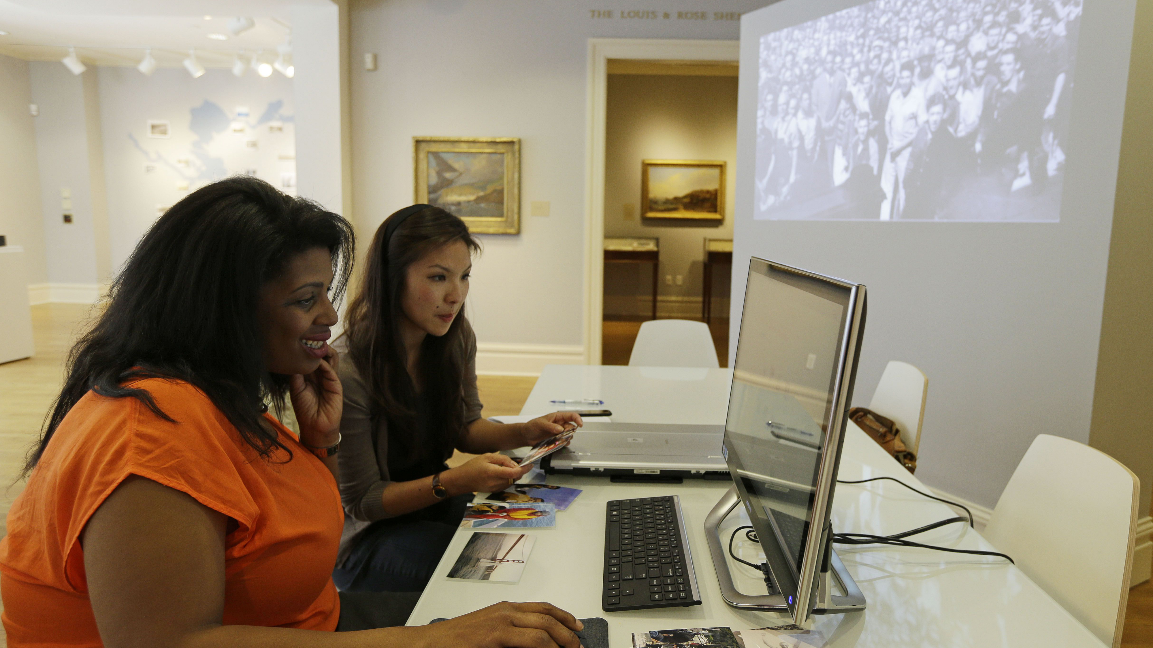 """In this photo taken Friday, April 12, 2013, Rue Mapp, left, with the help of Kerry Young, right, scans in a 1942 photo showing singer Paul Robeson serenading a sea of black and white workers at Oakland's Moore Dry Dock Corp., one of the area's first integrated shipping yards, into a new exhibit called, """"Curating the Bay: Crowdsourcing a New Environmental History,"""" at the California Historical Society in San Francisco. A new narrative and visual history of San Francisco Bay is being formed using two of the area's key resources: people and technology. The 142-year-old California Historical Society may seem an unlikely home to innovation, but the museum's curators and historians are using new technology to collect the stories and photographs of Bay Area people to augment its existing artifacts. (AP Photo/Eric Risberg)"""