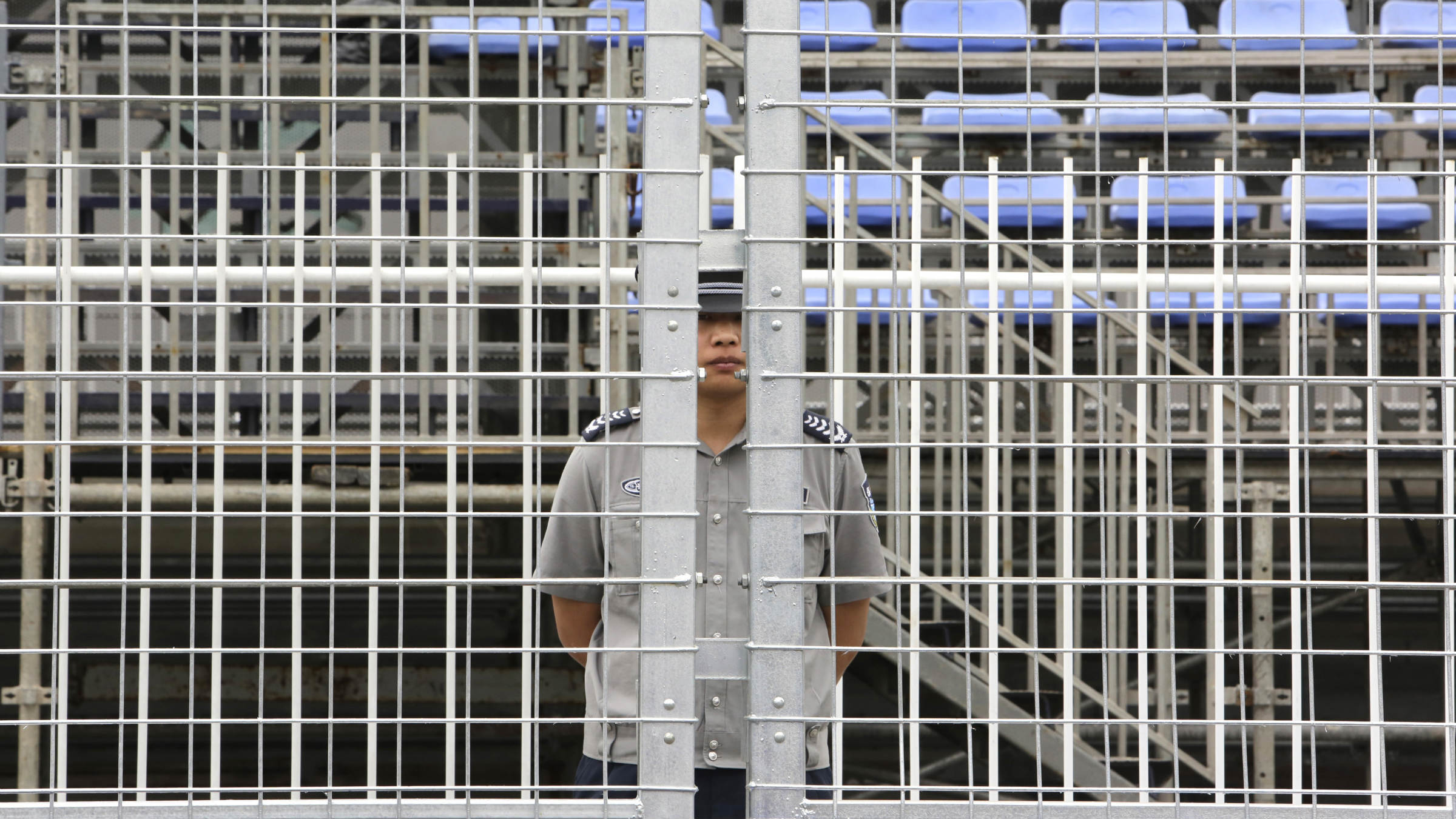 A security personnel stands guard behind a track fence ahead of the upcoming Formula E Championship race on Saturday in Beijing, September 12, 2014. The inaugural Formula E Championship, which according to its organisers is the world's first fully electric racing series, will be contested by 10 two-driver teams over 10 rounds. REUTERS/Jason Lee (CHINA - Tags: SPORT SCIENCE TECHNOLOGY MOTORSPORT)