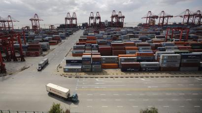 Container trucks drive past the container area at the Yangshan Deep Water Port, part of the newly announced Shanghai Free Trade Zone, south of Shanghai September 26, 2013. China has formally announced detailed plans for a new free-trade zone (FTZ) in Shanghai, touted as the country's biggest potential economic reform since Deng Xiaoping used a similar zone in Shenzhen to pry open a closed economy to trade in 1978. In an announcement on Friday from the State Council, or cabinet, China said it will open up its largely sheltered services sector to foreign competition in the zone and use it as a testbed for bold financial reforms, including a convertible yuan and liberalized interest rates. Economists consider both areas key levers for restructuring the world's second-largest economy and putting it on a more sustainable growth path. Picture taken on September 26, 2013. REUTERS/Carlos Barria (CHINA - Tags: POLITICS BUSINESS INDUSTRIAL TPX IMAGES OF THE DAY)