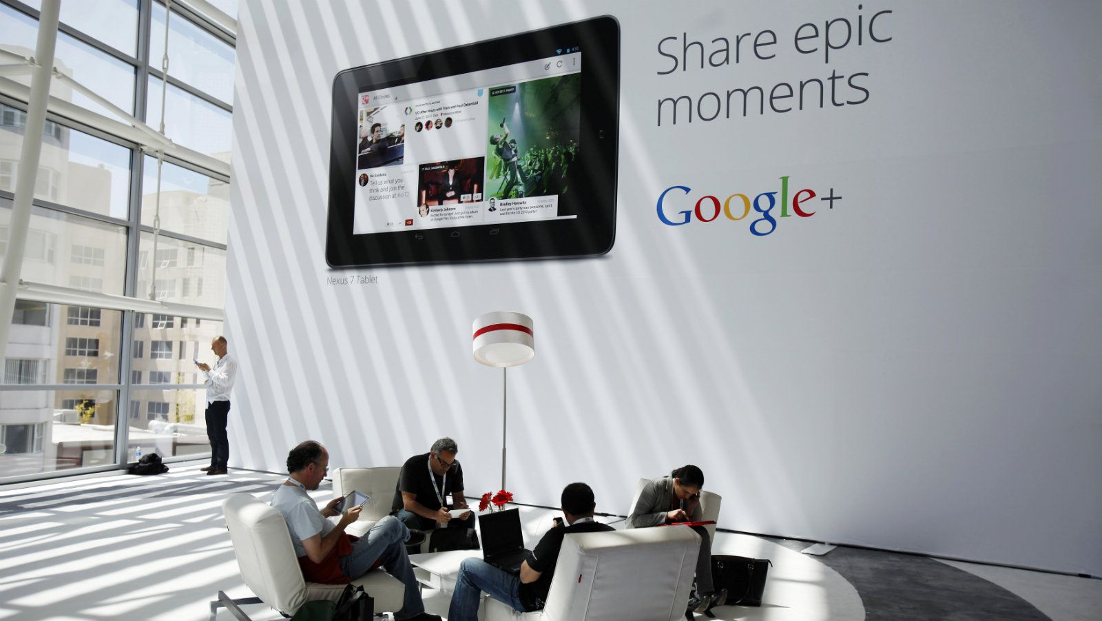 Attendees sits in front of a Google+ advertisment during Google I/O Conference at Moscone Center in San Francisco, California June 28, 2012. REUTERS/Stephen Lam (UNITED STATES)