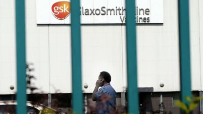 A security guard talks on his mobile phone as he patrols outside a GlaxoSmithKline factory in Shanghai July 16, 2013.