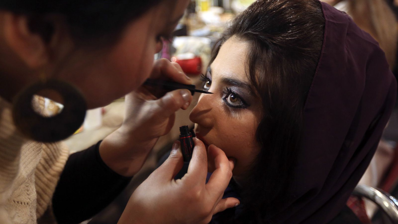 """Afghan's Latifa Azizi has her make up done before performing in the """"Afghan star"""" talent show in Kabul January 23, 2013. Azizi and her family fled Mazar for the Afghan capital, Kabul, soon after she appeared on the show in November. Her community was angry with her appearance, saying it was un-Islamic for a woman to sing and appear on television. The family began to receive death threats. Picture taken on January 23."""