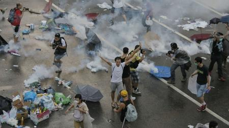 Protesters walk through tear gas used by riot police against protesters after thousands of people blocked a main road at the financial central district in Hong Kong, Sunday, Sept. 28, 2014
