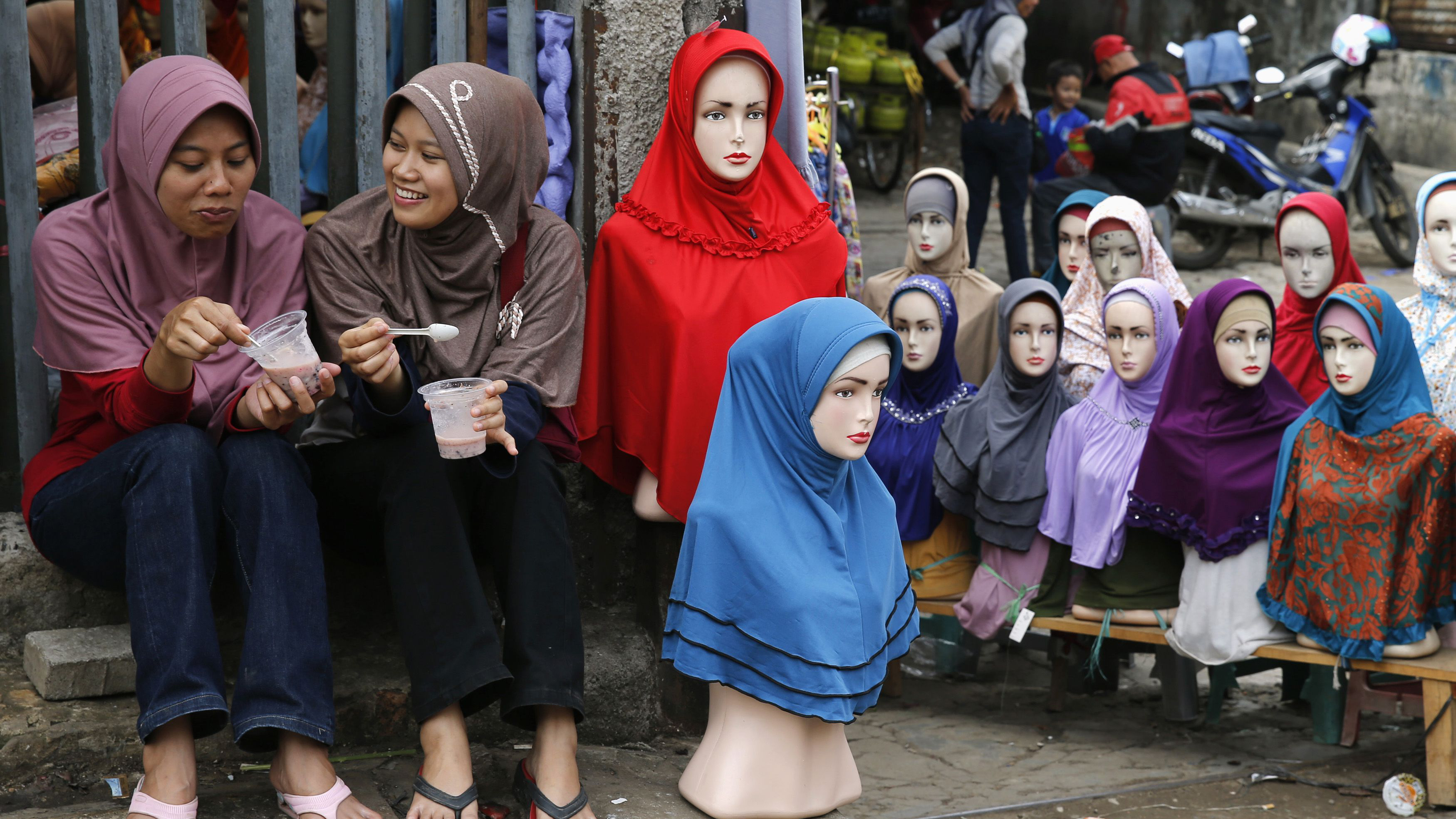 Girls sit near mannequins displaying hijabs for sale at Tanah Abang market, ahead of the holy fasting month of Ramadan, in Jakarta June 27, 2014. REUTERS/Beawiharta (INDONESIA - Tags: RELIGION BUSINESS SOCIETY TPX IMAGES OF THE DAY)