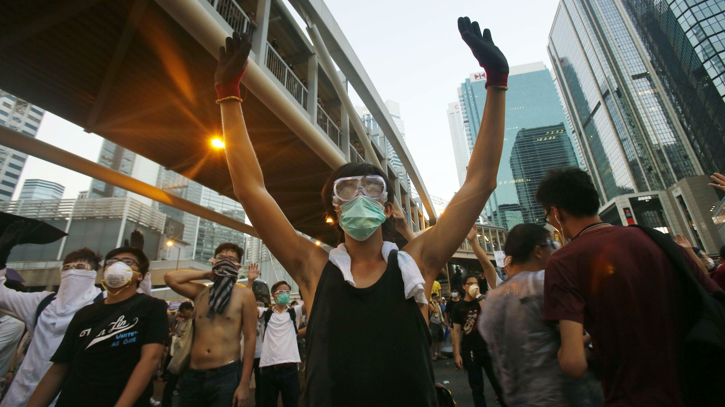 Student protesters occupy streets surrounding the government headquarters in Hong Kong, Sunday evening, Sept. 28, 2014. A tense standoff between thousands of Hong Kong pro-democracy protesters and police warning of a crackdown spiraled into an extraordinary scene of chaos Sunday as the crowd jammed a busy road and clashed with officers wielding pepper spray. (AP Photo/Wally Santana