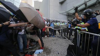 Protesters (L) use umbrellas to block pepper spray from riot policemen, as tens of thousands of protesters block the main street to the financial Central district outside the government headquarters in Hong Kong, September 28, 2014.