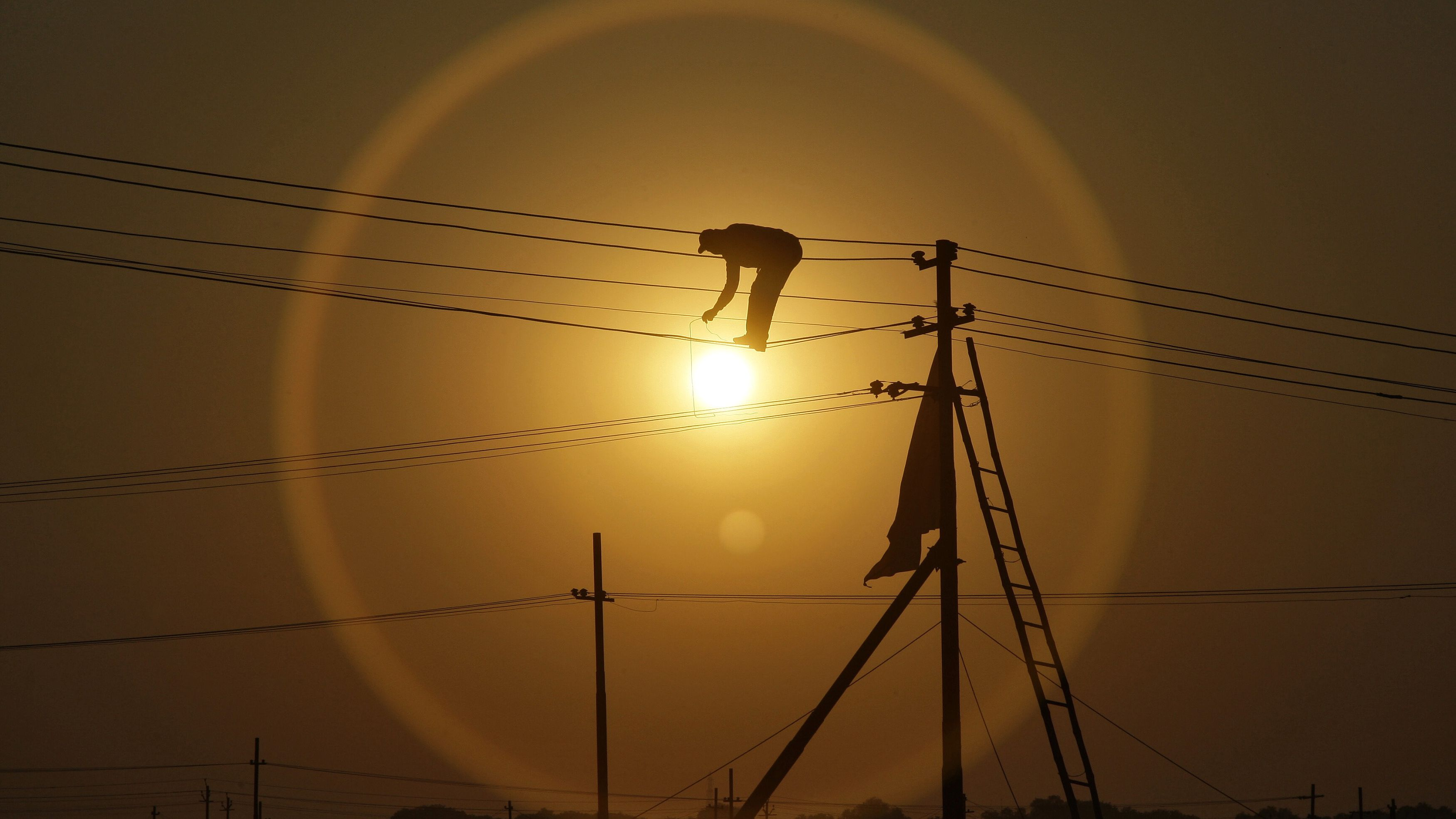 """An employee from the electricity board works on newly installed overhead power cables ahead of the """"Kumbh Mela"""", or Pitcher Festival, as the sun sets in the northern Indian city of Allahabad December 7, 2012. REUTERS/Jitendra Prakash (INDIA - Tags: ENERGY BUSINESS EMPLOYMENT TPX IMAGES OF THE DAY)"""