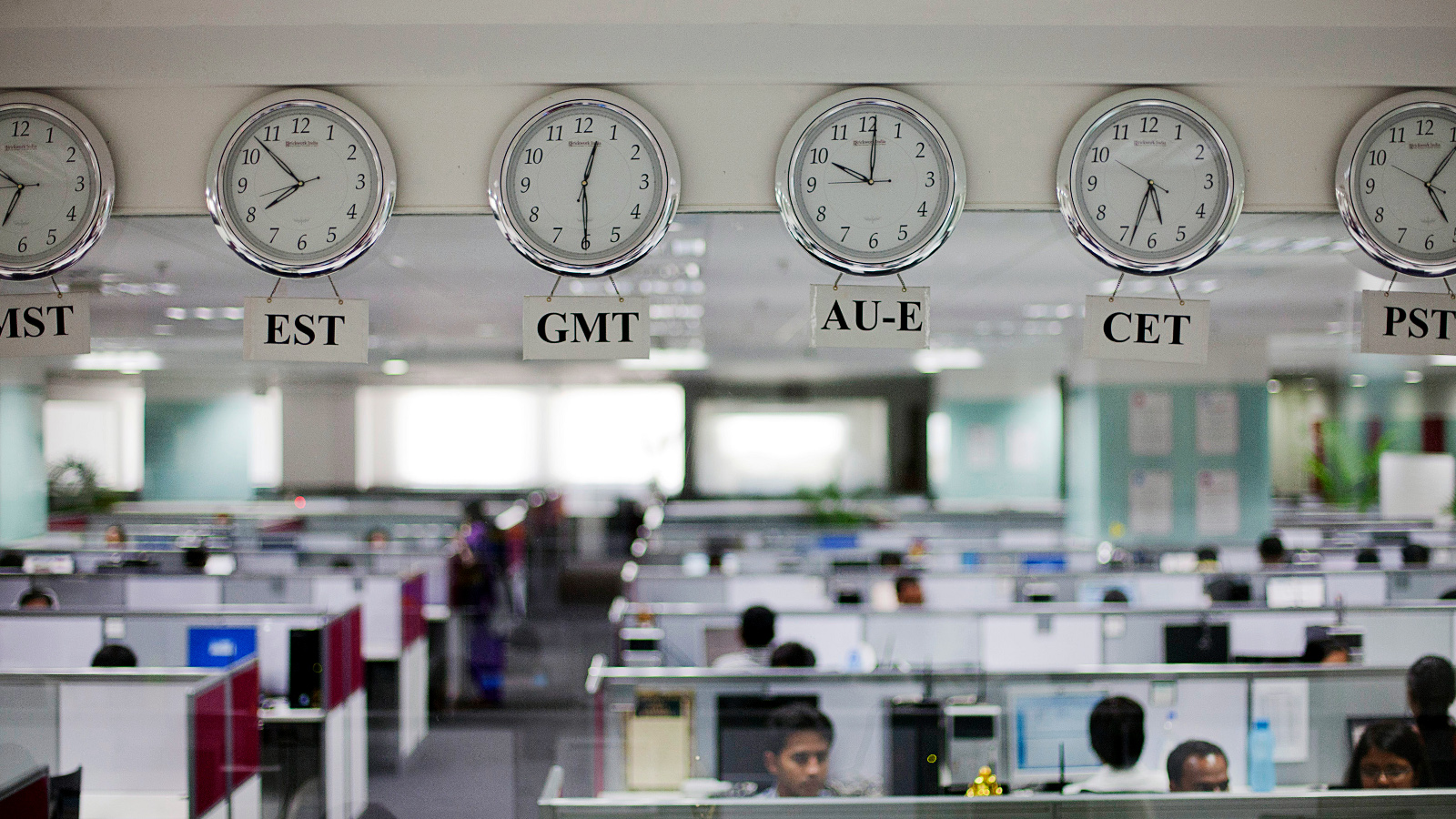 Workers are pictured beneath clocks displaying time zones in various parts of the world at an outsourcing centre in Bangalore, February 29, 2012. India's IT industry, with Bangalore firms forming the largest component, is now worth an annual $100 billion and growing 14 percent per year, one of the few bright spots in an economy blighted by policy stagnation and political instability. Picture taken on February 29, 2012.