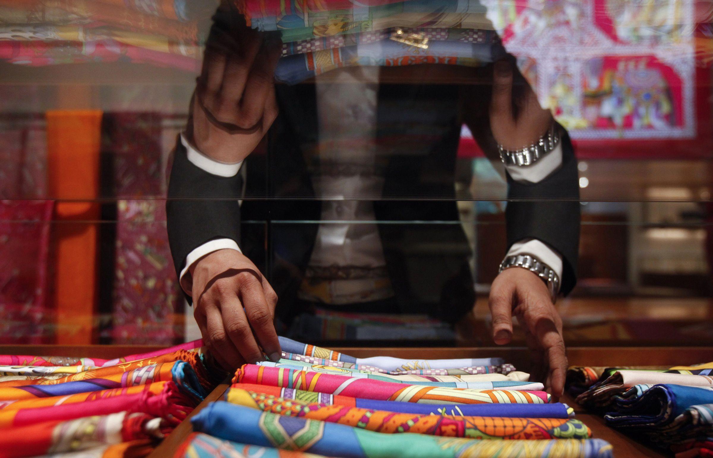 A saleswoman arranges scarves inside a Hermes showroom in Mumbai