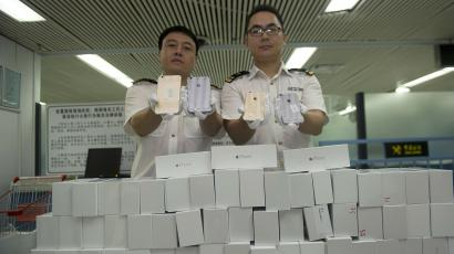 Customs officers pose for photographs as they display smuggled iPhone 6 sets, which were seized at the customs of a port in Shenzhen, near the Hong Kong border in Guangdong province