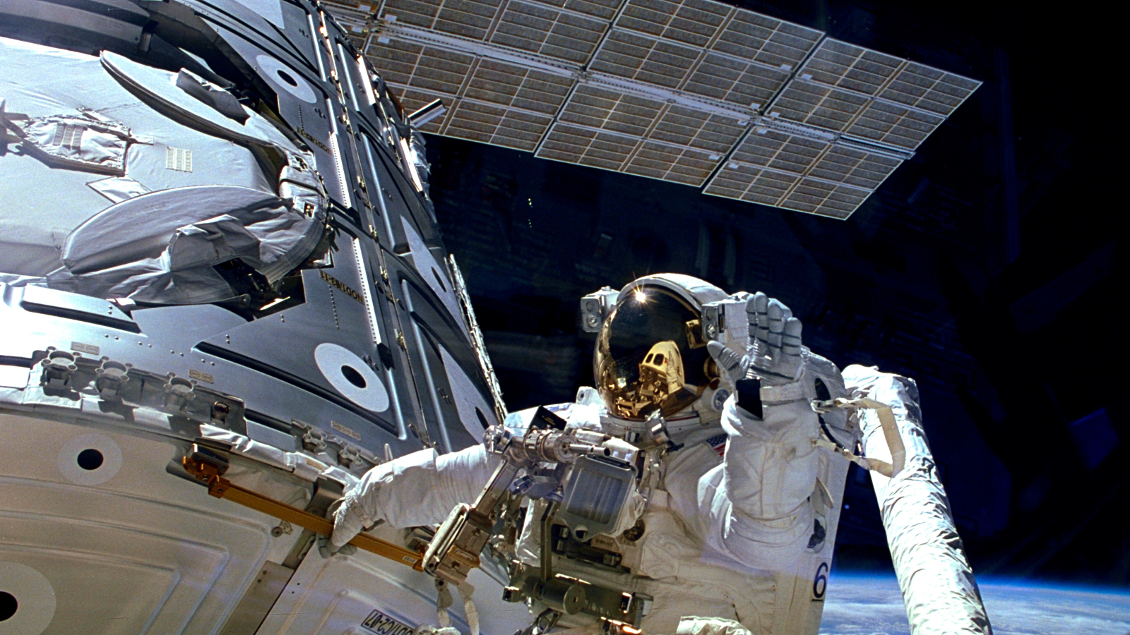 Astronaut James H. Newman waves during a spacewalk preparing for the release of the first combined elements of the International Space Station on November 20, 1998 in this image released on November 20, 2013. The Russian-built Zarya module, with its solar array panel visible here, was launched into orbit fifteen years ago on November 20, 1998. Two weeks later, on December 4, 1998, NASA's space shuttle Endeavour launched Unity, the first U.S. piece of the complex. During three spacewalks on the STS-88 mission, the two space modules built on opposite sides of the planet were joined together in space, making the space station truly international.