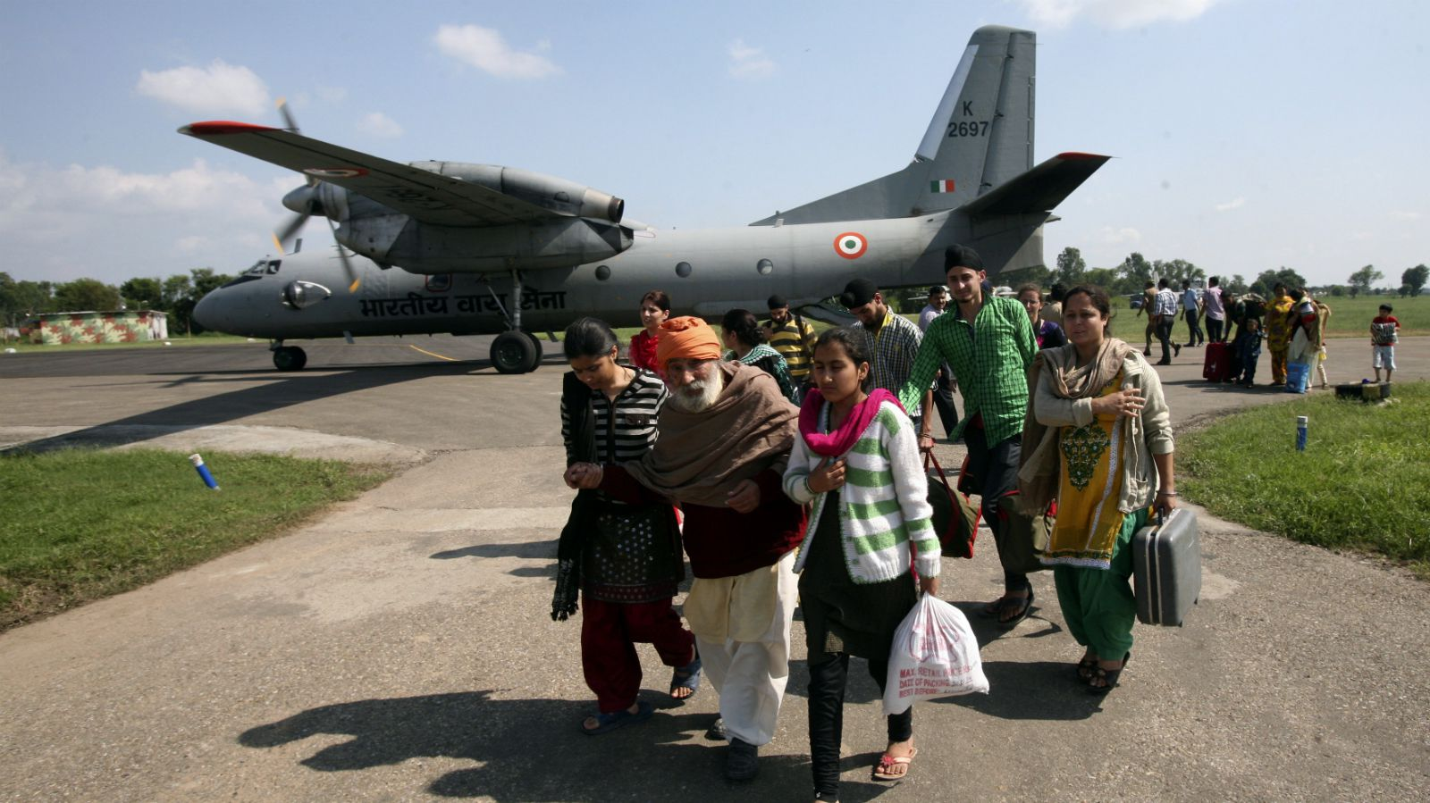 People, who were evacuated from flood-affected areas of Srinagar city, walk past an Indian Air Force AN-32 aircraft at an airport in Jammu September 9, 2014. The heaviest rains to fall on Kashmir in 50 years caught Indian and Pakistani authorities off guard, with criticism of their disaster preparedness growing on Tuesday as the number of dead hit 420 and thousands remained trapped on rooftops. On the Indian side of the heavily militarised de facto border that divides the Himalayan region, more than 2,000 villages and the city of Srinagar were submerged.