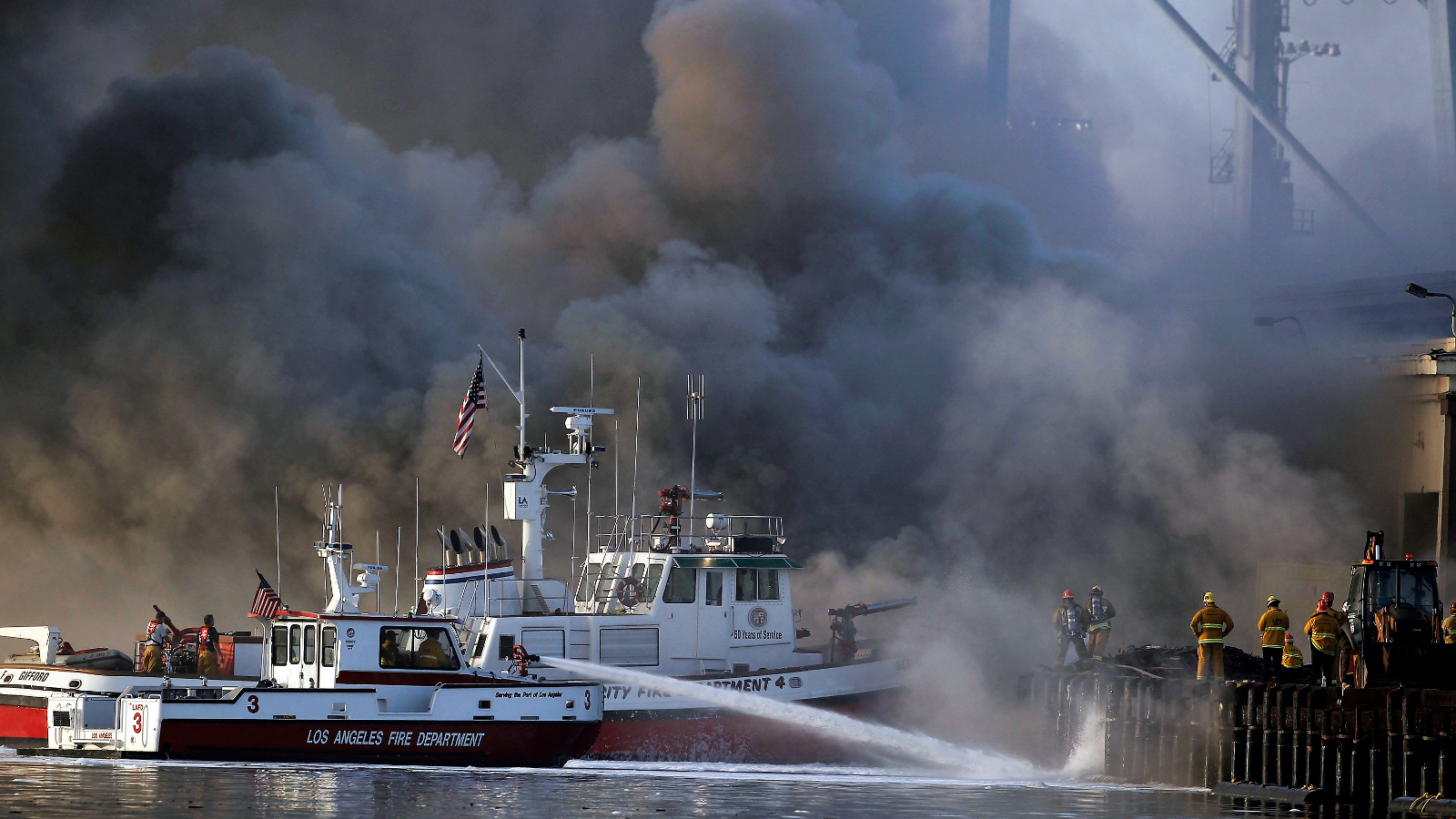 Los Angeles firefighters watch as smoke from a dock fire continues to rise at the Port of Los Angeles in the Wilmington section of Los Angeles on Tuesday, Sept 23, 2014. The fire that forced evacuations from the wharf continues to smolder but officials say it's under control. Nearly 12 hours after starting, the blaze is sending up huge plumes of smoke that is drifting over Los Angeles Harbor early Tuesday.