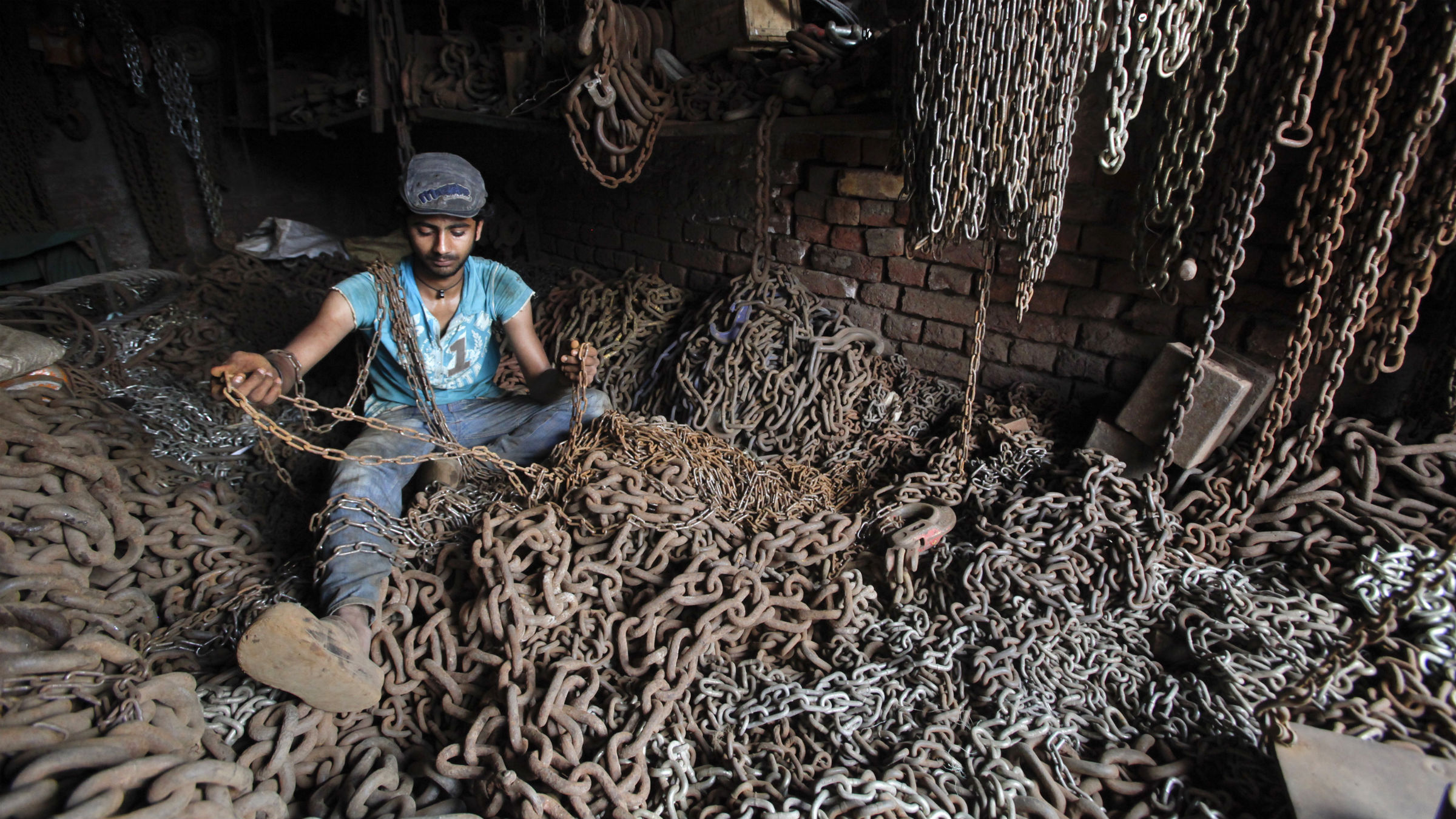 Man in room full of metal chains