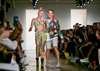 Miley Cyrus, left, joins fashion designer Jeremy Scott for a walk on the runway after he showed his Spring 2015 collection during New York Fashion Week