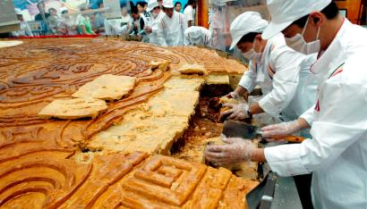 Chefs slice a giant mooncake measuring 8.15 meters in diameter and weighing approximately 22.5 metric tons for sale at a store in Shenyang, northeast China's Liaoning province September 9, 2007. The mooncake was made to celebrate the upcoming mid-autumn festival which falls on September 25. It costs about 10 yuan (1.33 USD) per 500 grams, local media reported. Picture taken September 9, 2007. REUTERS/China Daily (CHINA) CHINA OUT - RTR1TP8S