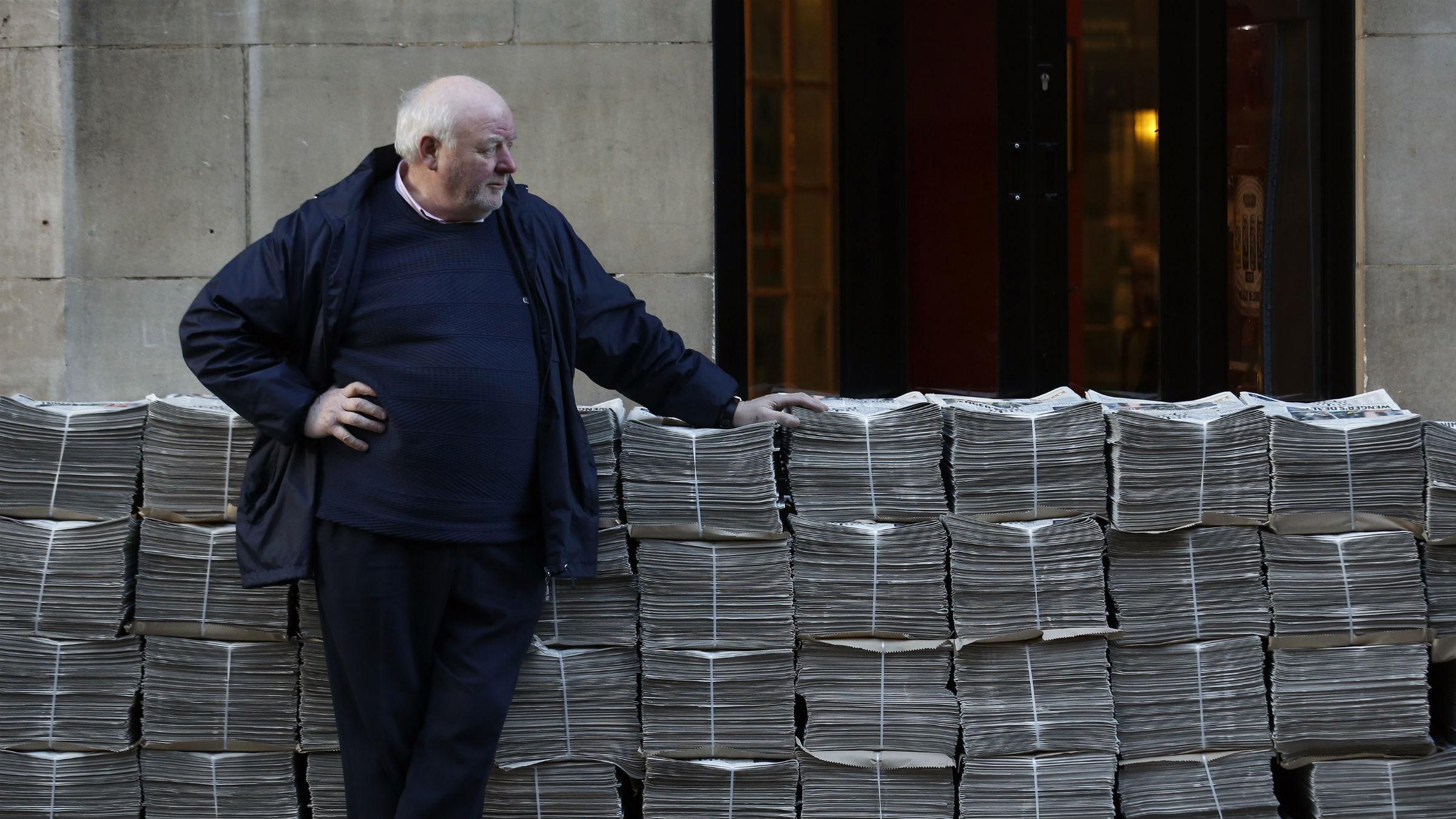 Man standing next to stacks of newspaper