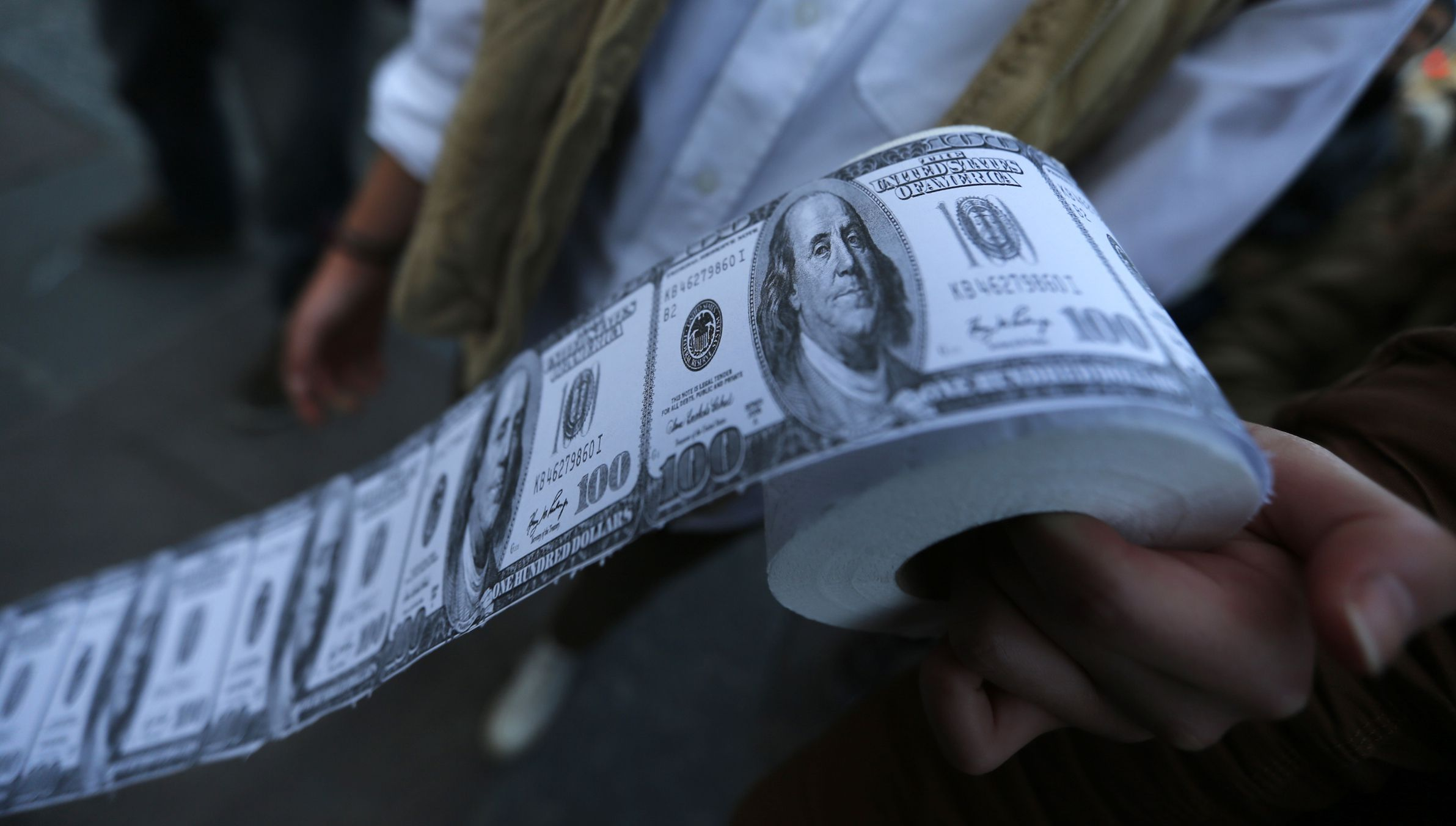 A demonstrator holds toilet paper made from fake U.S. dollars during a protest against Turkey's Prime Minister Tayyip Erdogan and his ruling Ak Party (AKP) government in Ankara February 27, 2014. An audio recording purporting to be of Erdogan giving his son business advice has been published on YouTube, following one earlier in the week that fuelled a corruption scandal and unnerved markets. Erdogan said a similar post on the video-sharing site YouTube on Monday, allegedly of him telling his son Bilal to dispose of large sums of cash as a graft investigation erupted, had been faked by his political enemies. REUTERS/Umit Bektas (TURKEY - Tags: POLITICS CIVIL UNREST CRIME LAW) - RTR3FSFR