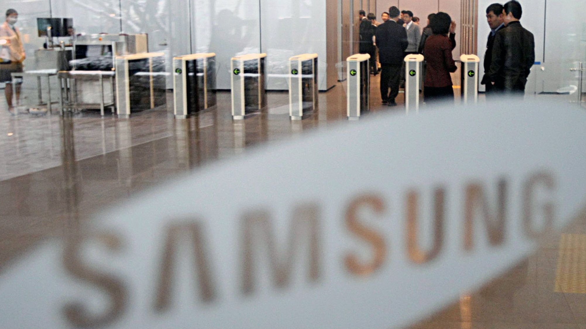 Employees of Samsung are seen next to a logo at Samsung Electronics head office in Seoul, South Korea, Friday, Jan. 16, 2009. Samsung Electronics Co. said Friday it will consolidate four key businesses _ semiconductors, liquid crystal displays, mobile phones and televisions _ into two divisions as the company deals with the slowing global economy.(AP Photo/ Yonhap, Kim Ju-sung)