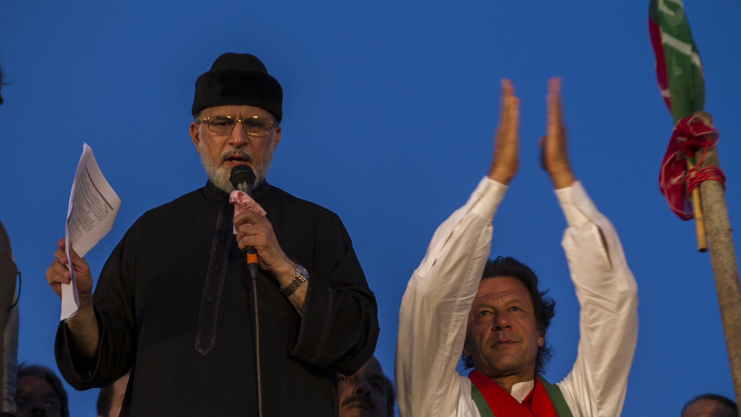 Tahirul Qadri, Sufi cleric and opposition leader of political party Pakistan Awami Tehreek (PAT), addresses supporters while flanked by Imran Khan (R), chairman of the opposition Pakistan Tehreek-e-Insaf (PTI) political party, in Islamabad