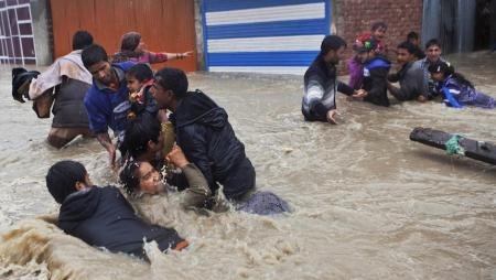 Kashmiri residents wade through floodwaters in Srinagar.