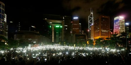 Pro-democracy protesters hold up their mobile phones during a campaign to kick off the Occupy Central civil disobedience event in front of the financial Central district in Hong Kong