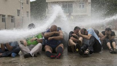 Pro-democracy activists are hit with water during a drill to simulate the scenario of being sprayed with a water cannon at the upcoming