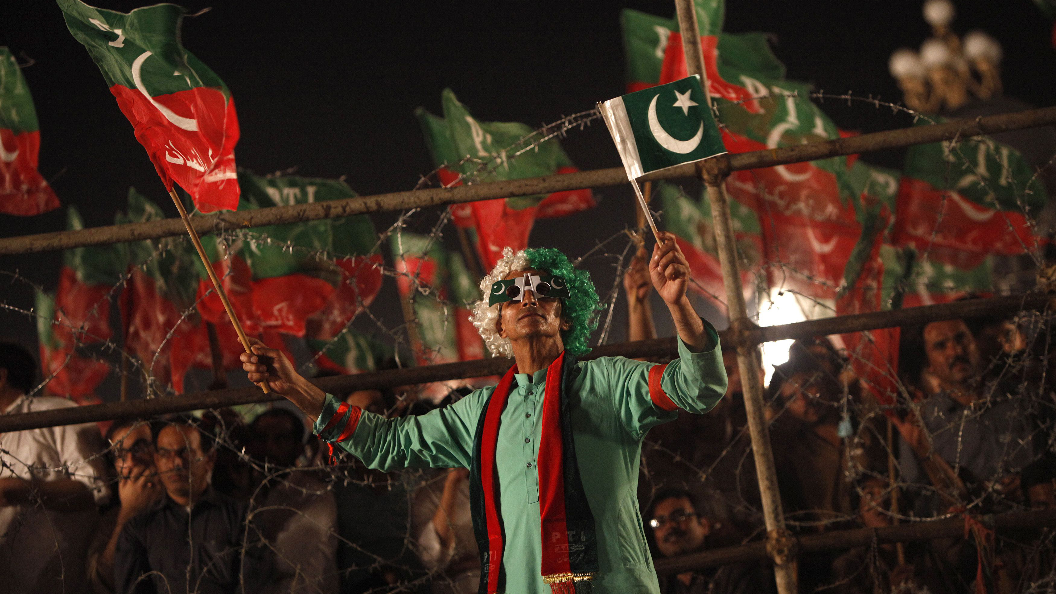 "A supporter of the chairman of the Pakistan Tehreek-e-Insaf (PTI) political party Imran Khan waves national and party flags while listening to him speak during what has been dubbed a ""freedom march"" in Islamabad August 26, 2014. Protesters led by cricketer-turned-politician Imran Khan and firebrand cleric Tahir ul-Qadri have vowed to occupy the capital, Islamabad, until Sharif resigns - a demand the premier has firmly rejected. REUTERS/Akhtar Soomro (PAKISTAN - Tags: POLITICS CIVIL UNREST TPX IMAGES OF THE DAY)"