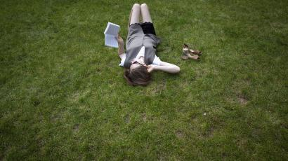 A woman lies in the grass while reading a book, at Columbia University in New York, April 14, 2014. The temperature reached an unseasonably high 77 Fahrenheit (25 Celsius). REUTERS/Carlo Allegri (UNITED STATES - Tags: SOCIETY ENVIRONMENT EDUCATION)