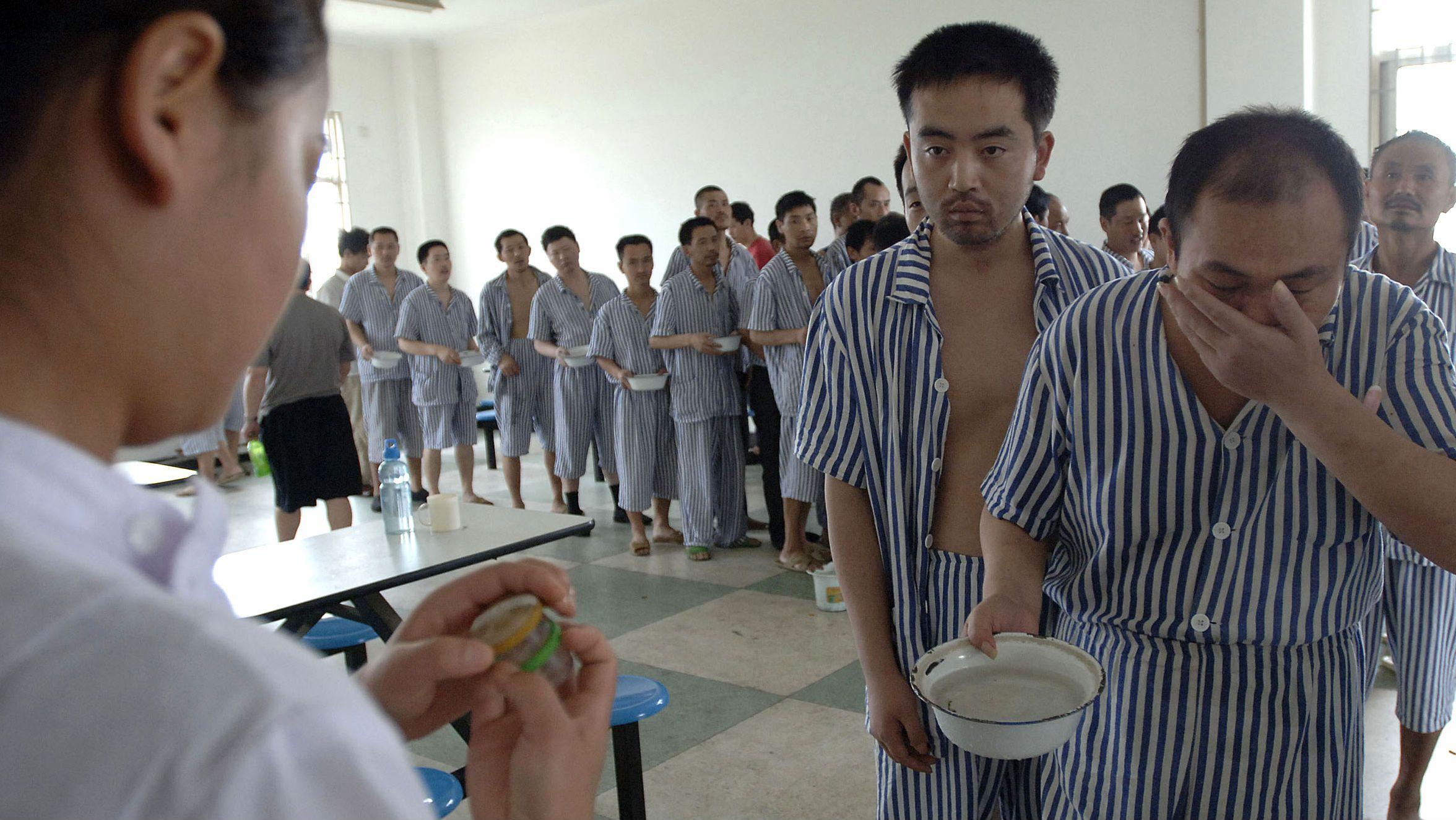 Inmates line up to take medicine in the presence of nurses at a hospital which houses and provides treatment to about 100 patients who are suffering from mental disorders, in Hefei, east China's Anhui province July 3, 2007. Just 10 percent of the 30 million Chinese currently suffering from depression are getting proper medical care due to a lack of psychiatrists and social prejudice against mental illness, experts have said, China Daily reported. REUTERS/Jianan Yu (CHINA)