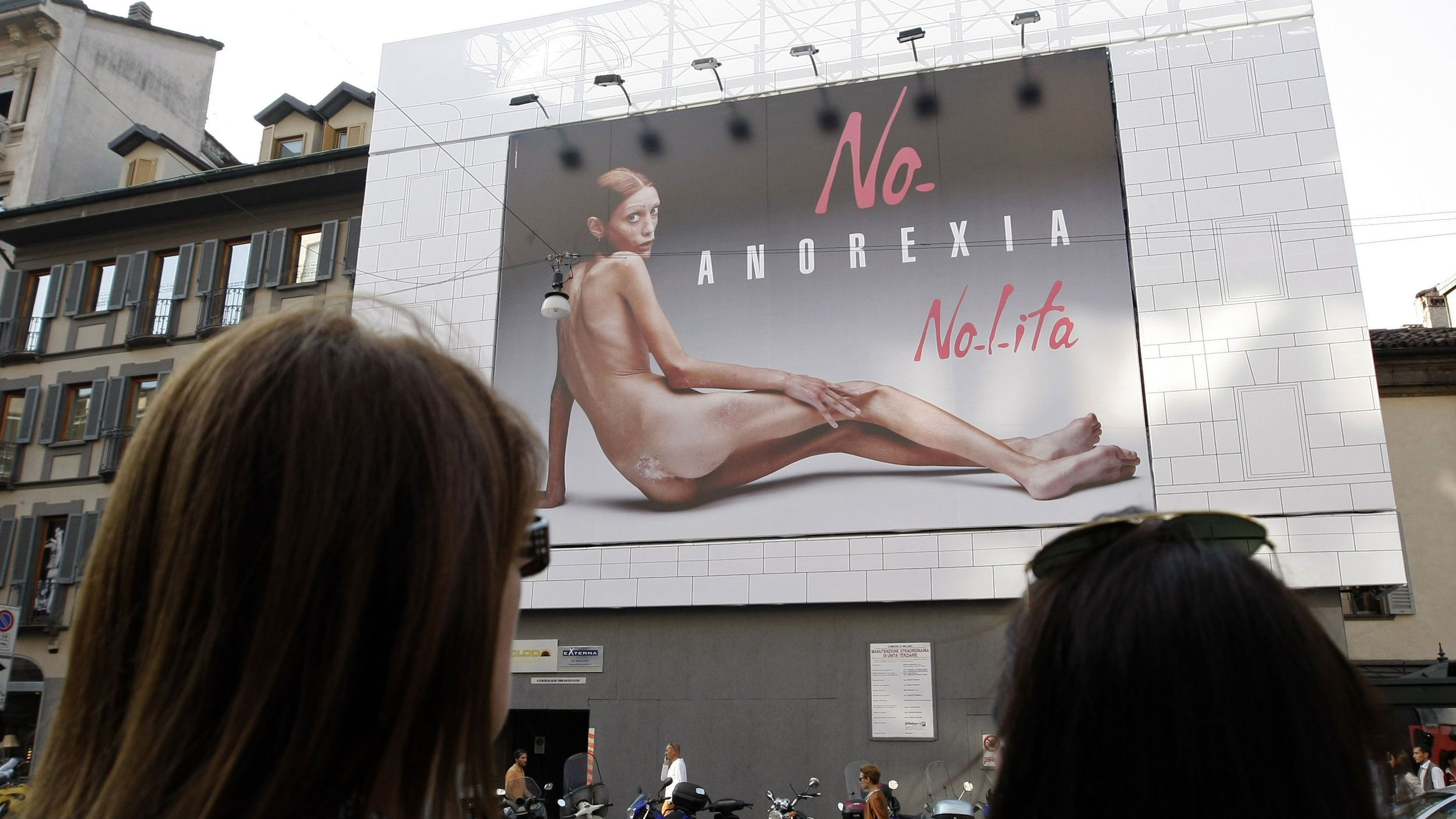 Two women look at an advertising board showing a shockingly emaciated naked woman in Milan September 24, 2007. The picture used to promote a fashion brand, appeared on Monday in double page spreads in Italian newspapers and on city billboards to coincide with fashion week in Milan. REUTERS/Stefano Rellandini (ITALY)