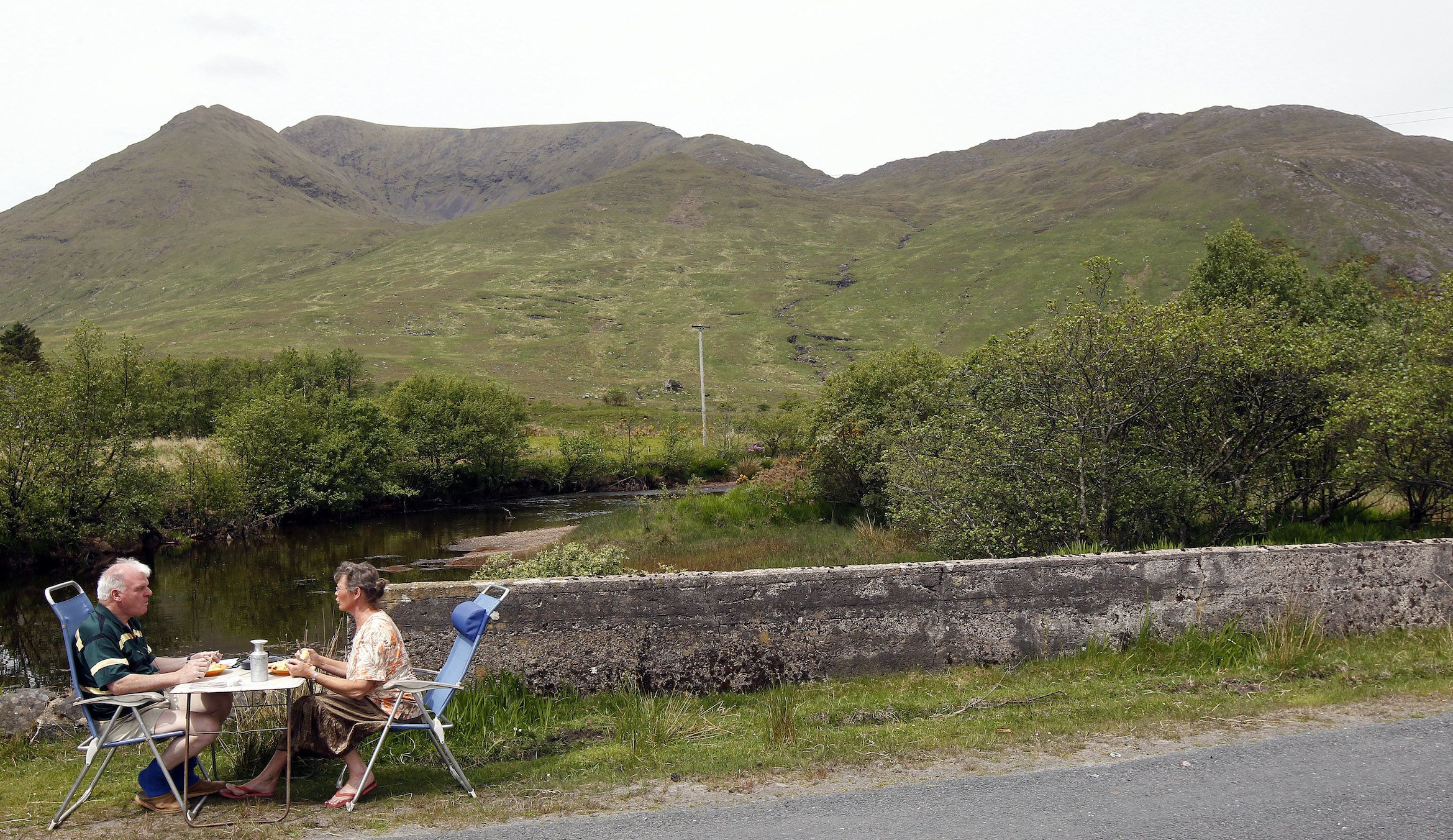 Tourists eat their lunch by the roadside in the Doo Lough Pass near the town of Wesport in County Galway on the West Coast of Ireland May 30, 2010. REUTERS/Cathal McNaughton (IRELAND - Tags: SOCIETY TRAVEL) - RTR2EKB0