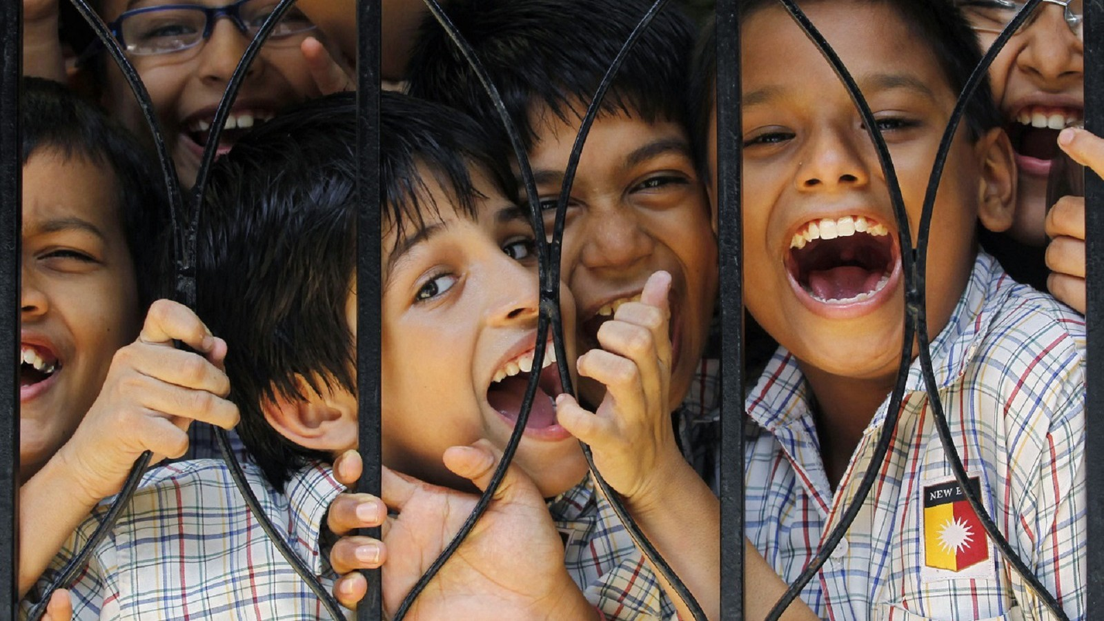 Boys react to the camera during their recess break in the middle of their academic day at a school in Mumbai August 10, 2010. The Right to Education Act that came into force has made free and compulsory education the right of every child between the age of 6 to 14 years old in India. UNESCO says the Act has brought the country closer to meeting its millennium development goals, with an estimated eight million out-of-school Indian children now having better access to education. REUTERS/Danish Siddiqui (INDIA - Tags: EDUCATION) - RTR2H7NJ