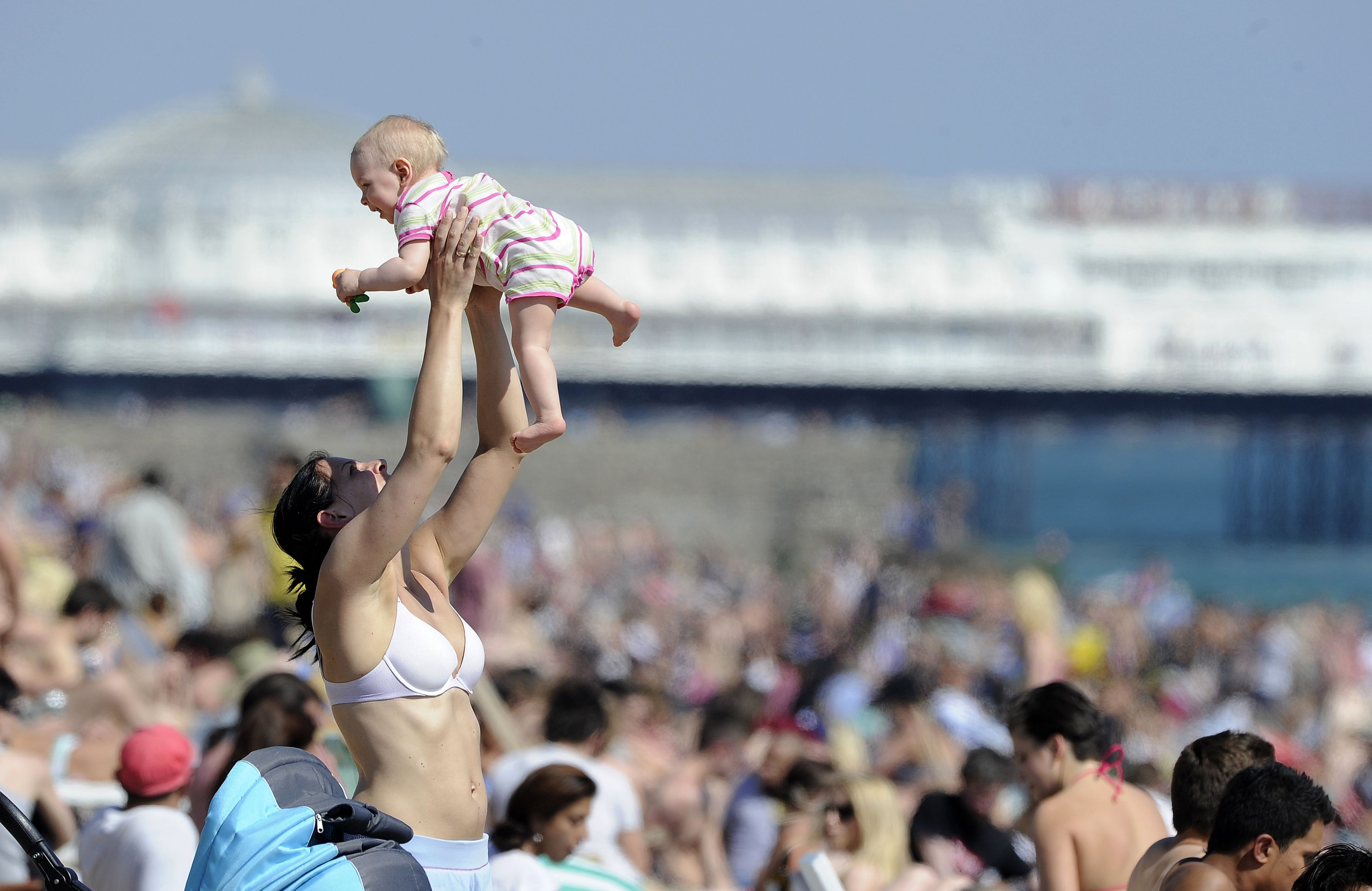 Sunbathers soak up the warmth on Brighton beach, in southern England May 26, 2012. REUTERS/Paul Hackett