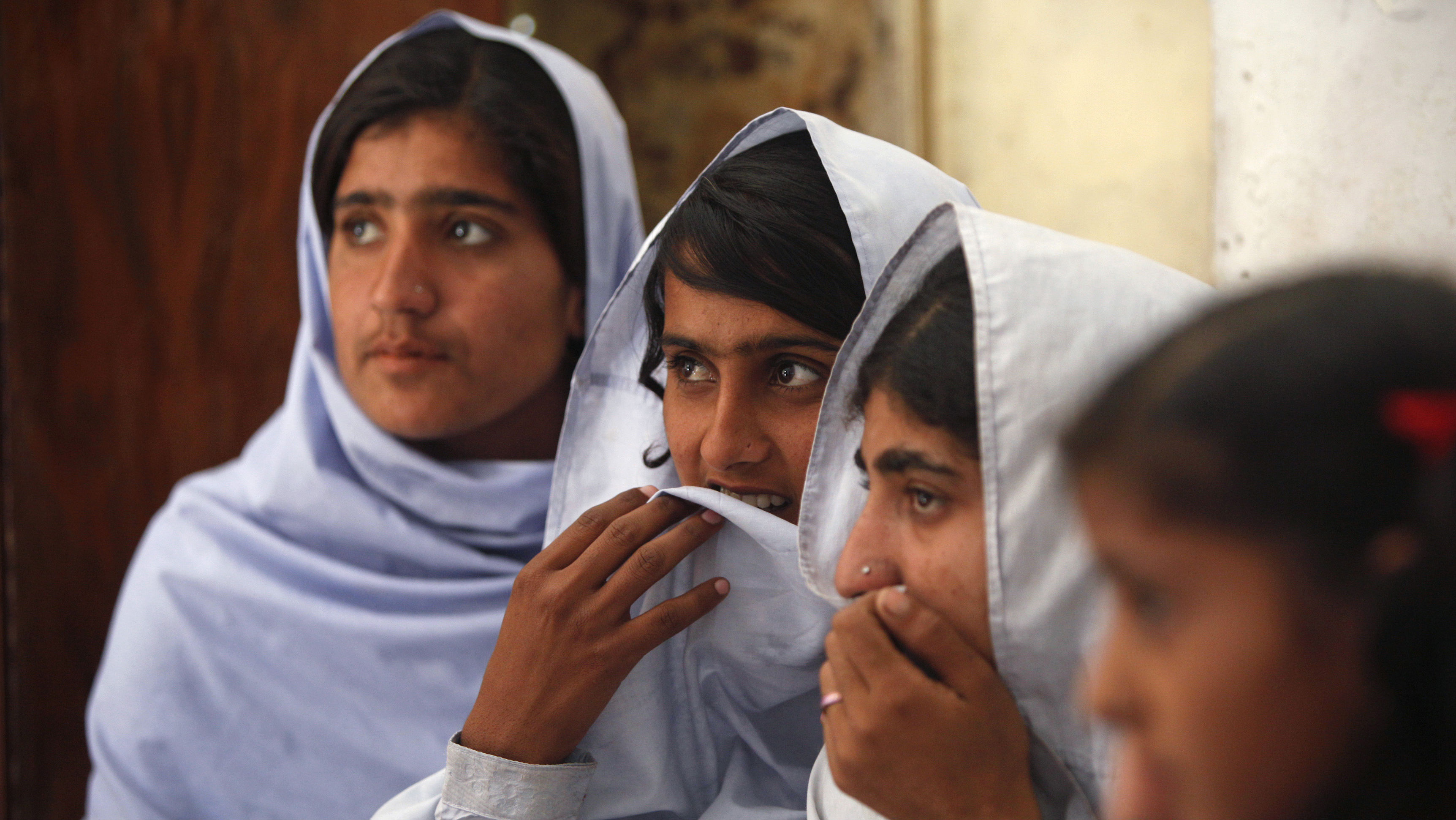 Students react while attending a lecture on preventive measures to take when sexual harassment occurs, during a class in Shadabad Girls Elementary School in Pir Mashaikh village in Johi, some 325 km (202 miles) from Karachi February 12, 2014. Sex education is common in Western schools but these ground-breaking lessons are taking place in deeply conservative rural Pakistan, a Muslim nation of 180 million people. Picture taken February 12, 2014. REUTERS/Akhtar Soomro (PAKISTAN - Tags: EDUCATION)