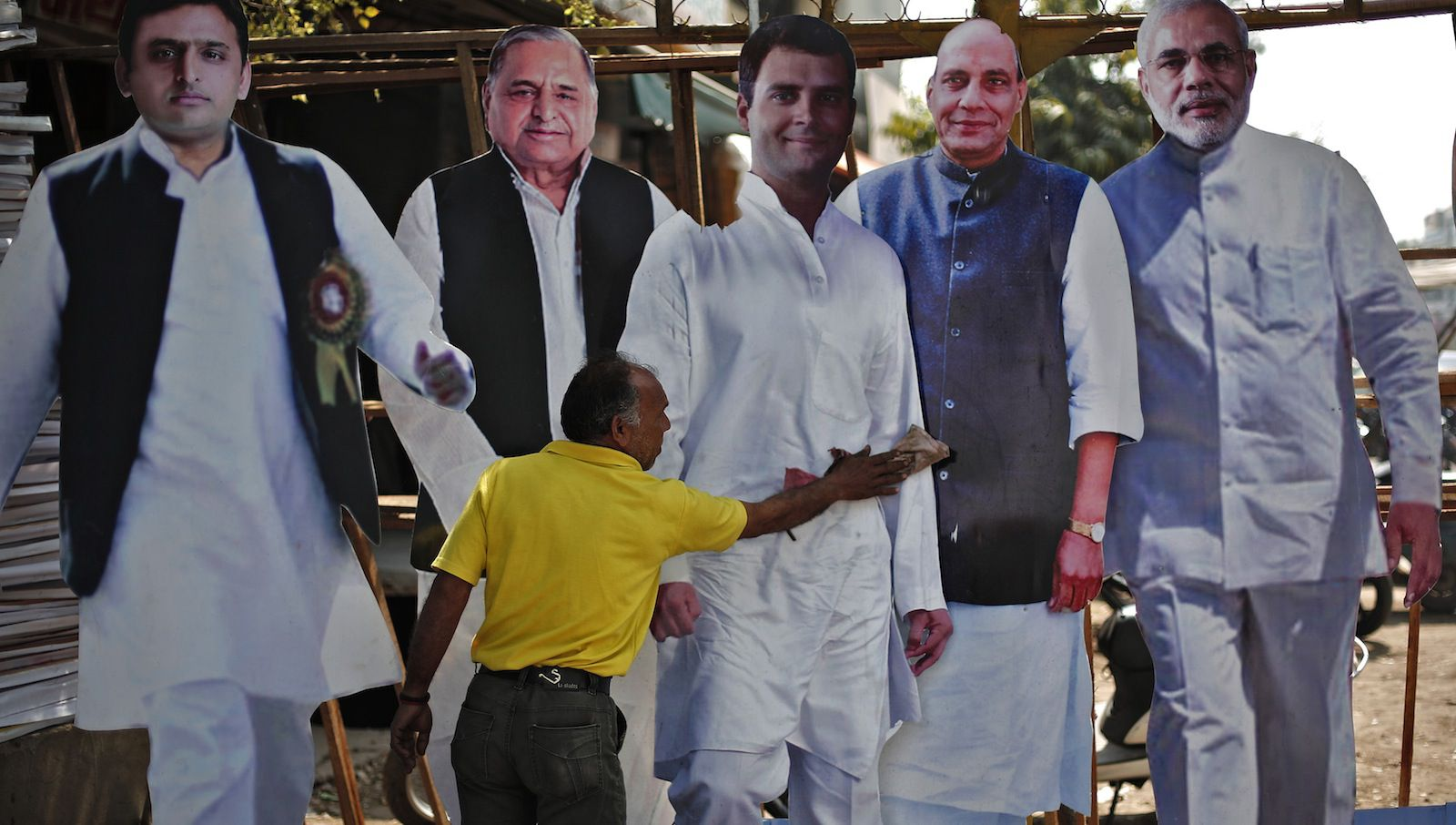 A worker cleans a cut-out of Rahul Gandhi (C) India's ruling Congress party Vice President, beside cut-outs of (L-R) Uttar Pradesh Chief Minister Akhilesh Yadav, Akhilesh's father and chief of Samajwadi Party Mulayam Singh Yadav, India's main opposition Bharatiya Janata Party President Rajnath Singh and Hindu nationalist Narendra Modi, prime ministerial candidate for BJP, as they are put on display for sale ahead of general elections in Ghaziabad, on the outskirts of New Delhi, March 24, 2014. The world's largest democracy goes to the ballot box next month. REUTERS/Adnan Abidi (INDIA - Tags: POLITICS ELECTIONS) - RTR3IBM2