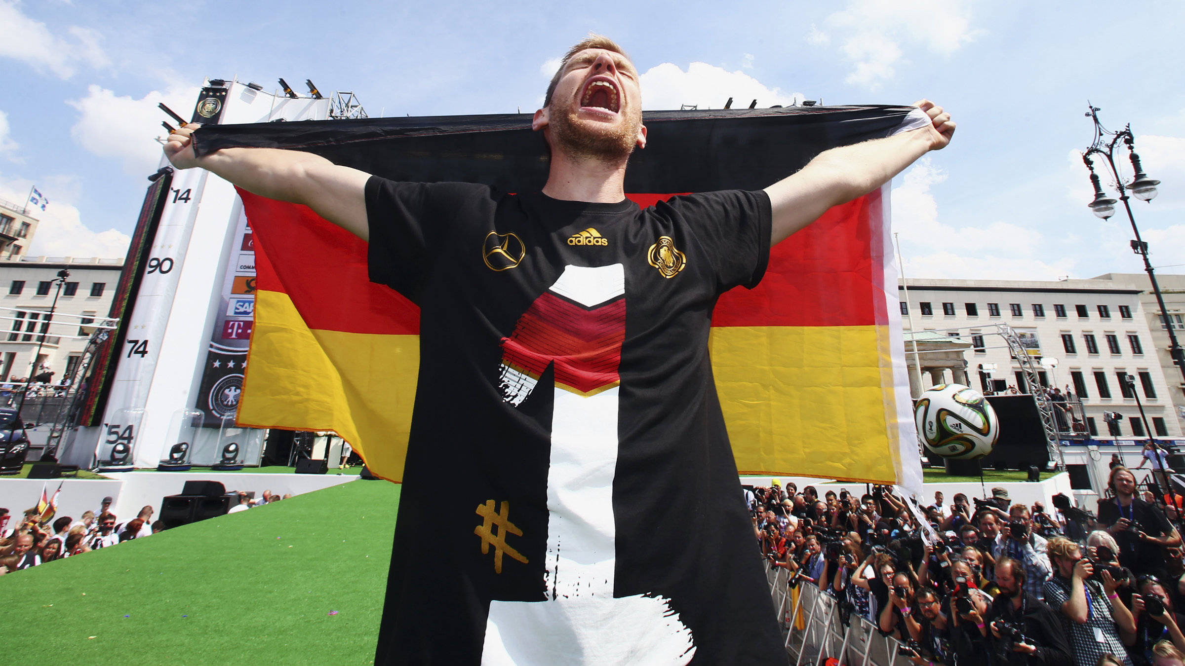 A German man holds his country's flag.